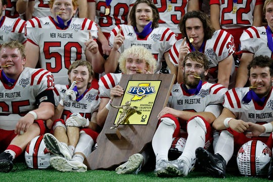 The New Palestine Dragons are awarded the championship trophy after winning the IHSAA Class 5A football State Championship game between New Palestine High School and Decatur Central High School, held at Lucas Oil Stadium on Saturday, Nov. 24, 2018.