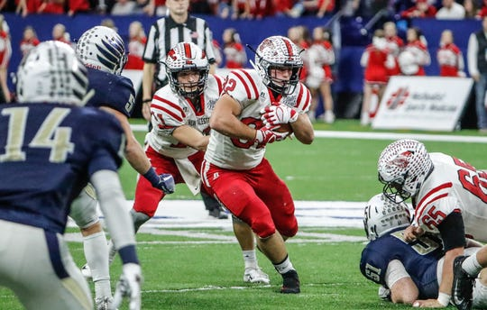 New Palestine's Charlie Spegal (32), runs the ball up the middle during the IHSAA Class 5A football State Championship game between New Palestine High School and Decatur Central High School, held at Lucas Oil Stadium on Saturday, Nov. 24, 2018.