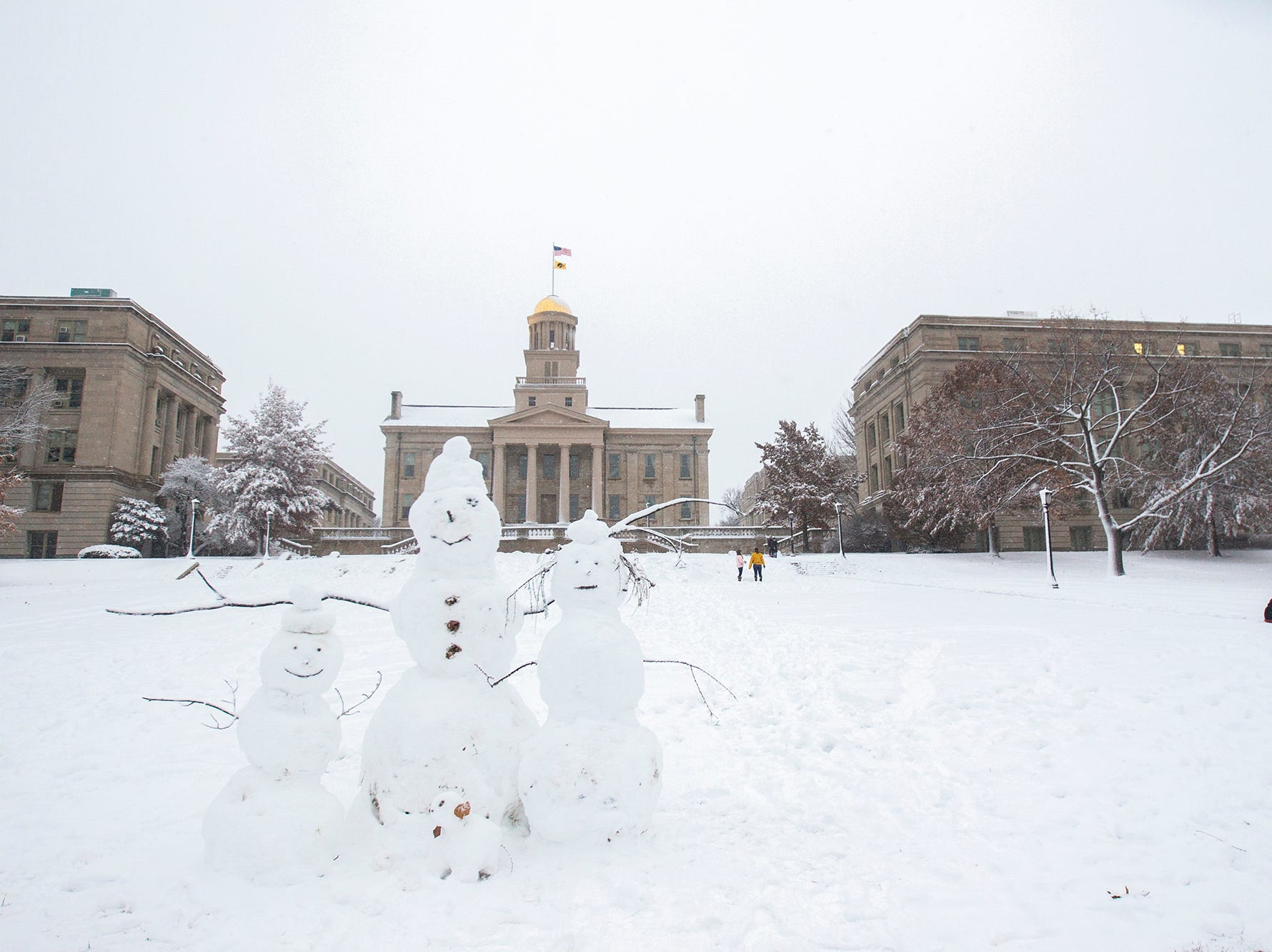 A family of snowmen sit together while people play in the snow on Sunday, Nov. 25, 2018, on the west side of the Pentacrest in Iowa City.