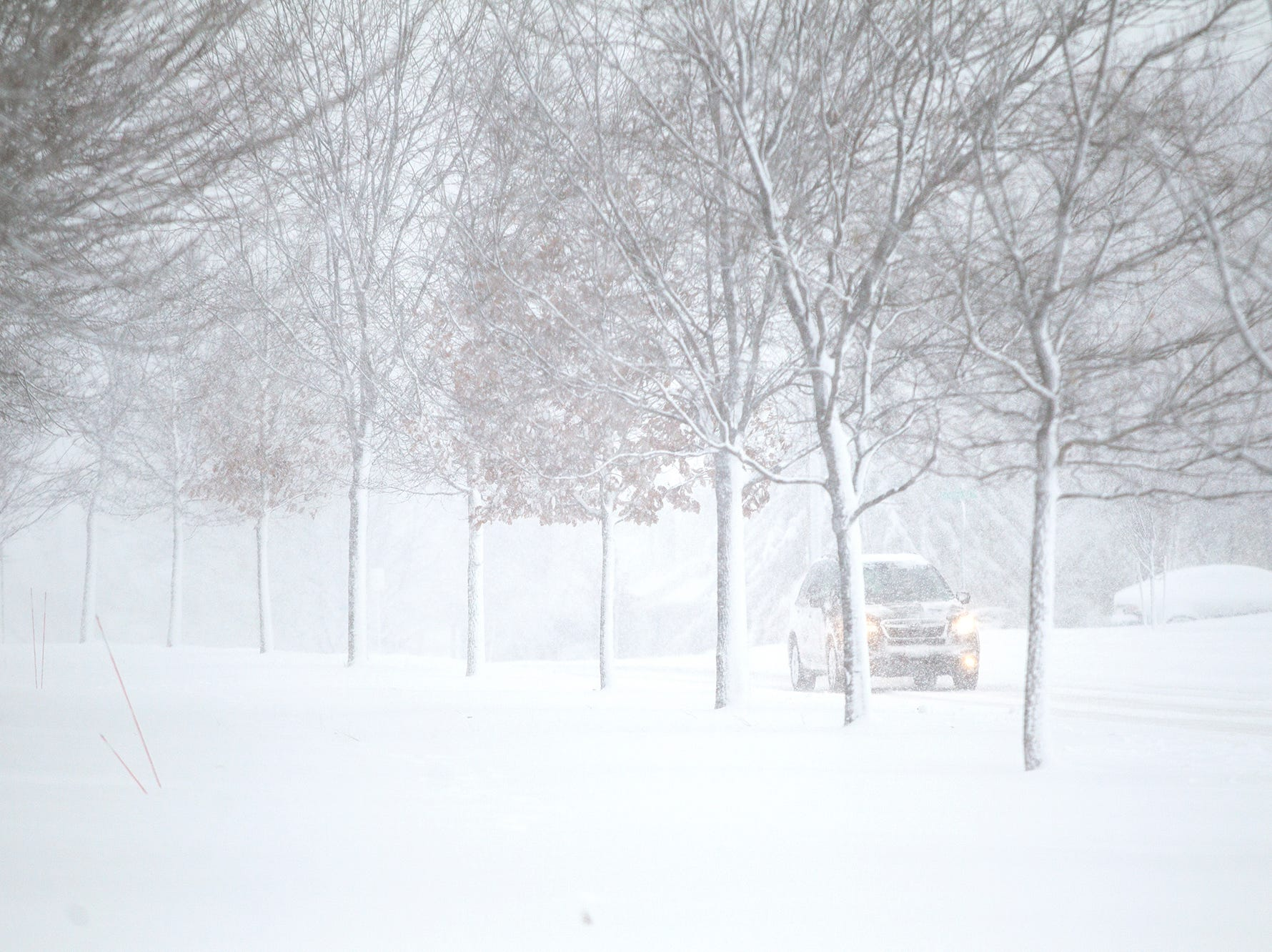 A car drives along Court Street as snow falls during a storm on Sunday, Nov. 25, 2018, on the east side of Iowa City. AccuWeather anticipated Iowa City to have a total of 6-10 inches of snow.