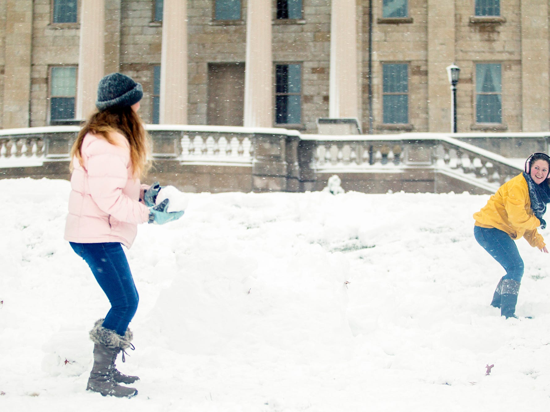 University of Iowa freshman Sarah Nighswonger, right, and Caroline Pickart throw snowballs during a snow storm on Sunday, Nov. 25, 2018, on the west side of the Pentacrest in Iowa City.