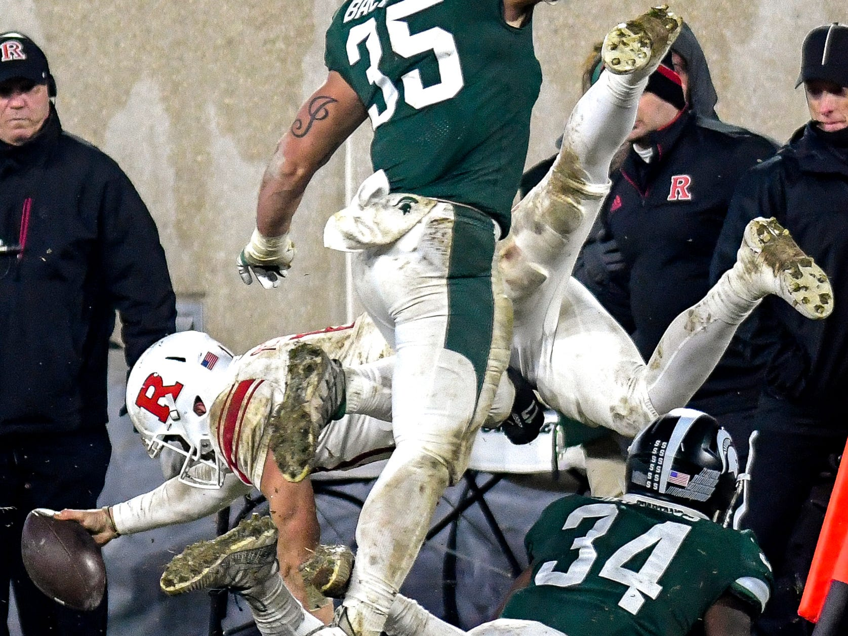 Rutgers quarterback Giovanni Rescigno dives as Michigan State's Joe Bachie and Antjuan Simmons, below, defend during the fourth quarter on Saturday, Nov. 24, 2018, at Spartan Stadium in East Lansing.