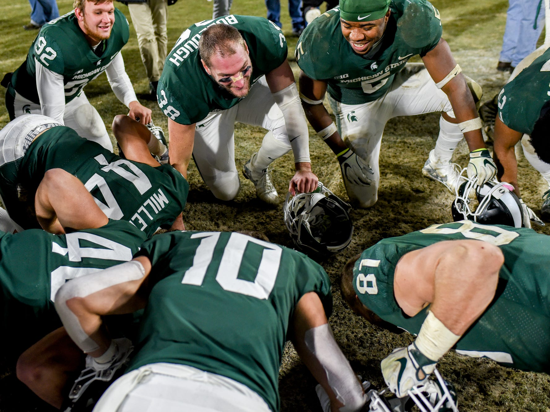 Michigan State senior all gather to kiss the Spartans helmet on the field after defeating Rutgers on Saturday, Nov. 24, 2018, at Spartan Stadium in East Lansing.