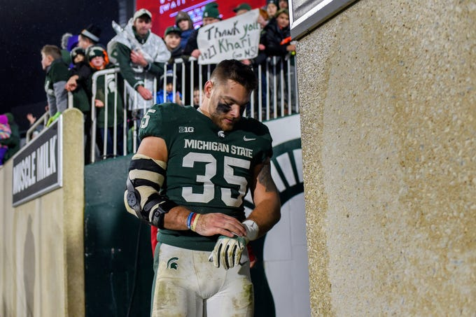 Michigan State's Joe Bachie takes off his gloves for a fan after the game on Saturday, Nov. 24, 2018, at Spartan Stadium in East Lansing.