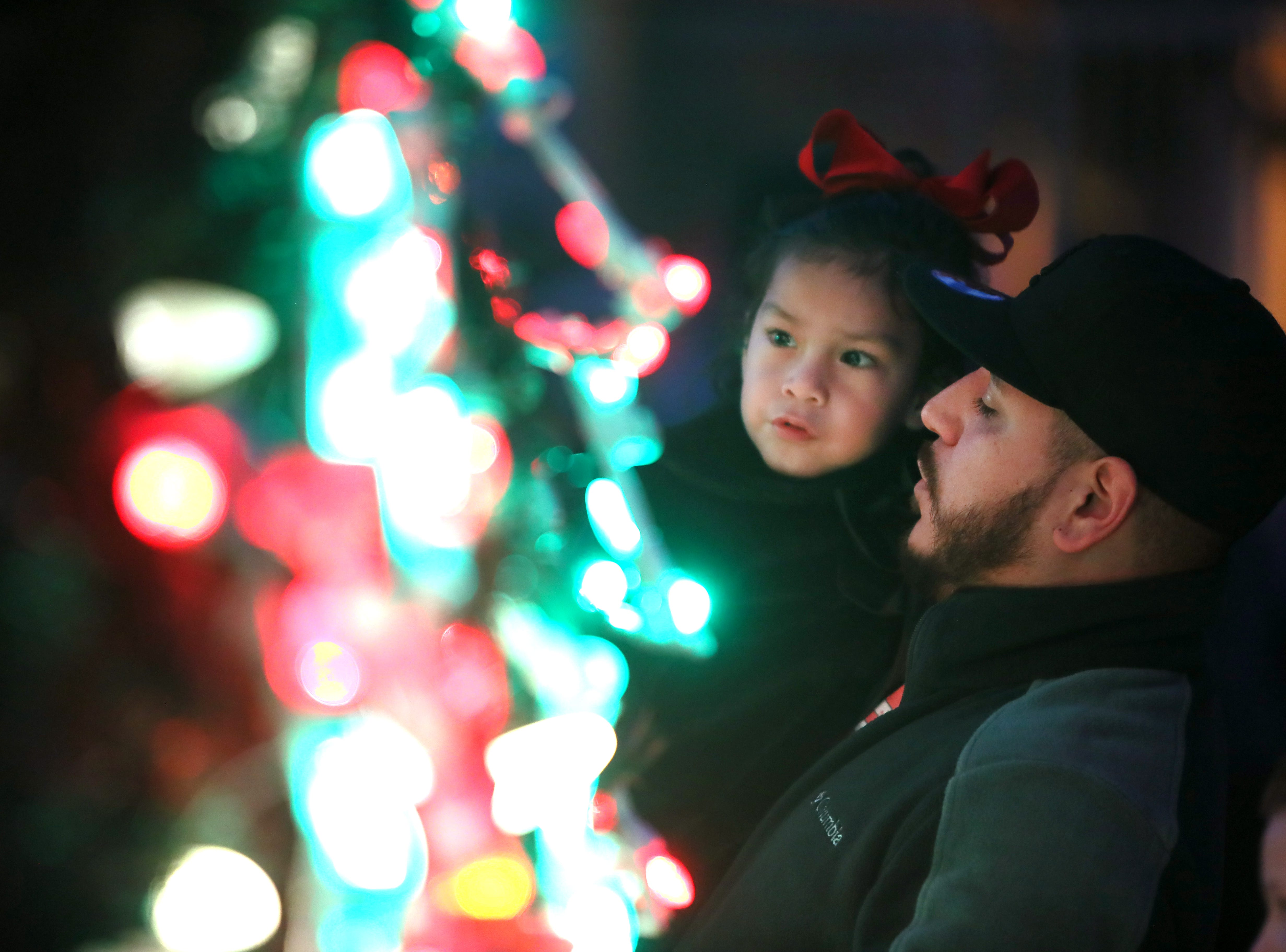 Alex Mercado holds Ximena Orozco, 3, for a closer look at the Christmas tree lights during Zoo Lights, a holiday event at the Memphis Zoo Saturday, Nov. 24, 2018.