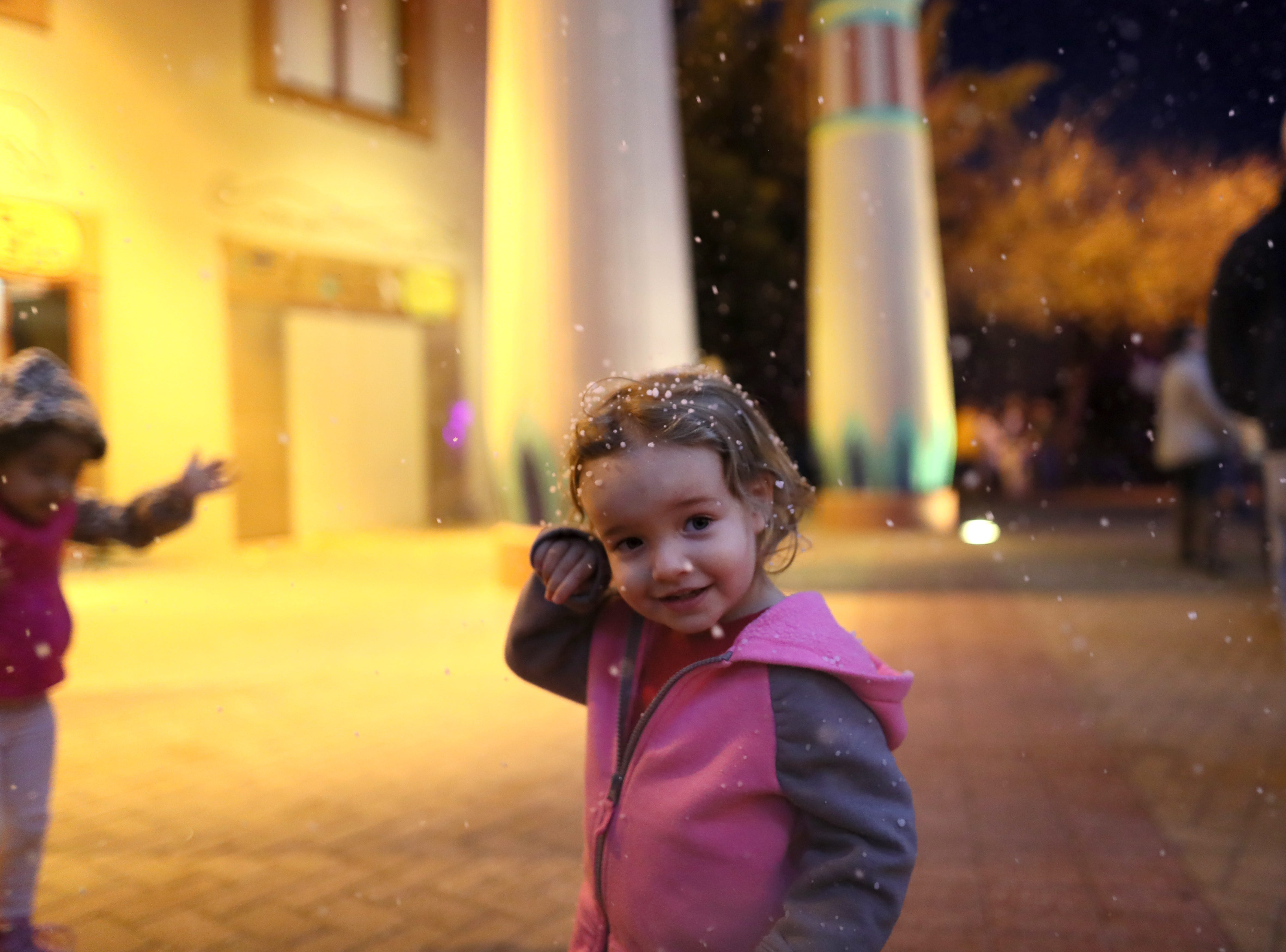 Isabella Uglesich 2, stands under the falling snow, manufactured for guests as they enter Zoo Lights a holiday season event at the Memphis Zoo Saturday, Nov. 24, 2018.