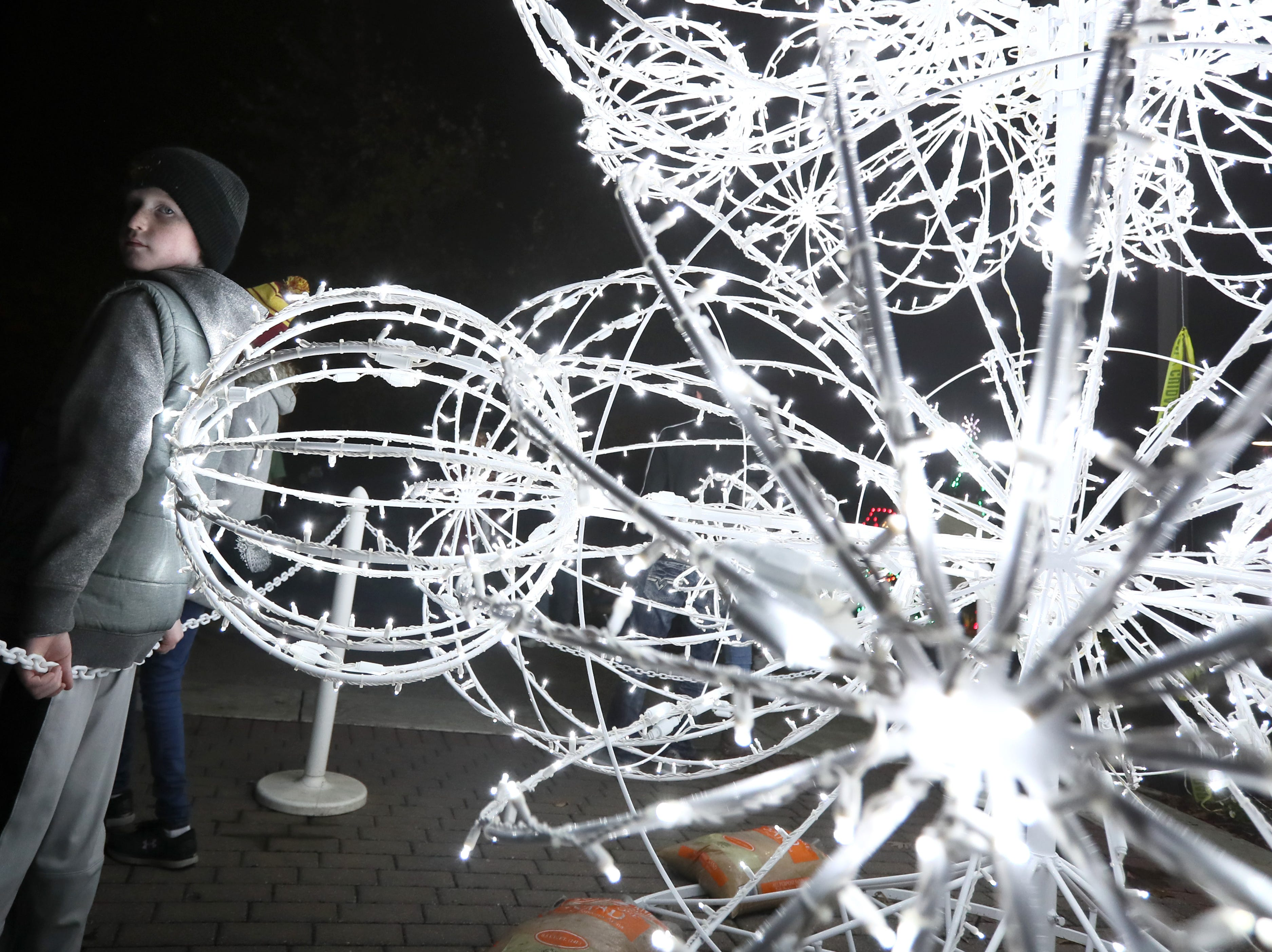Chris Pannell, 10, stands next to a lit scuplture during Zoo Lights, a holiday season themed event at the Memphis Zoo Saturday, Nov. 24, 2018.