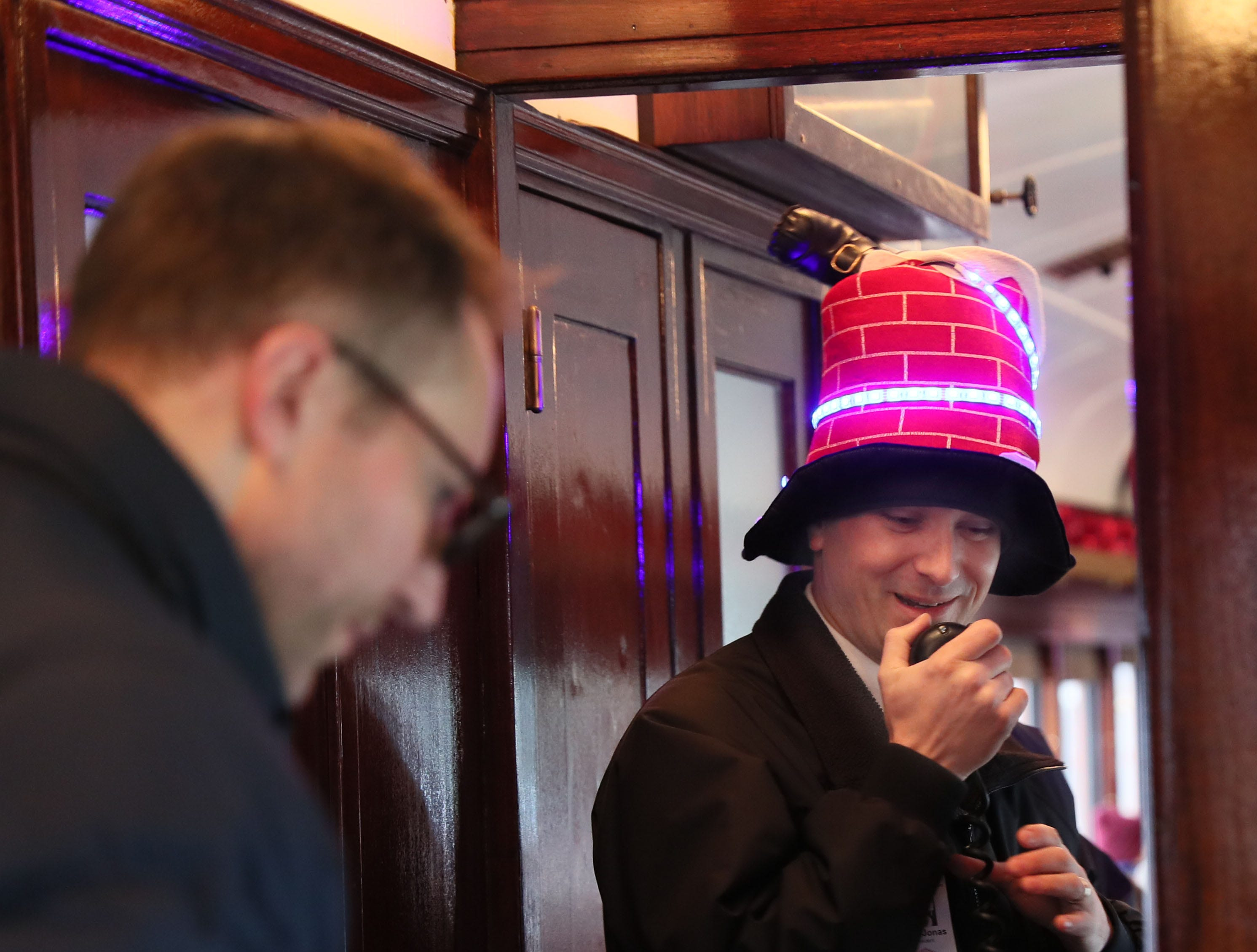Conductor Ryan Jonas makes announcements to the passengers. His hat depicts Santa going down a chimney headfirst.