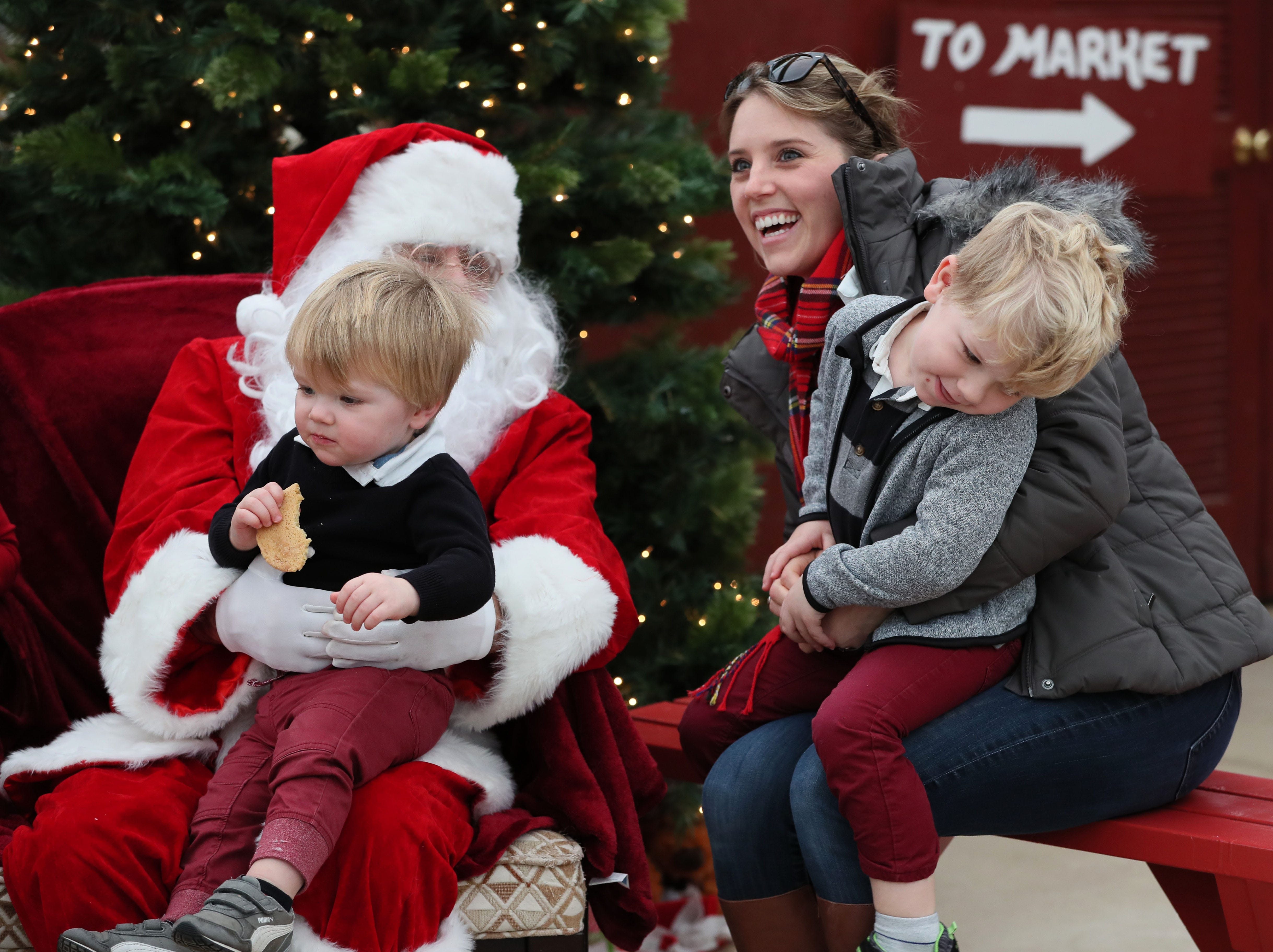 Danielle Wampole of Lake Mills coaxes her children, Emmett (right), 3, and  Graham, 1, into having their picture taken with Santa, aka Blase Catanese.