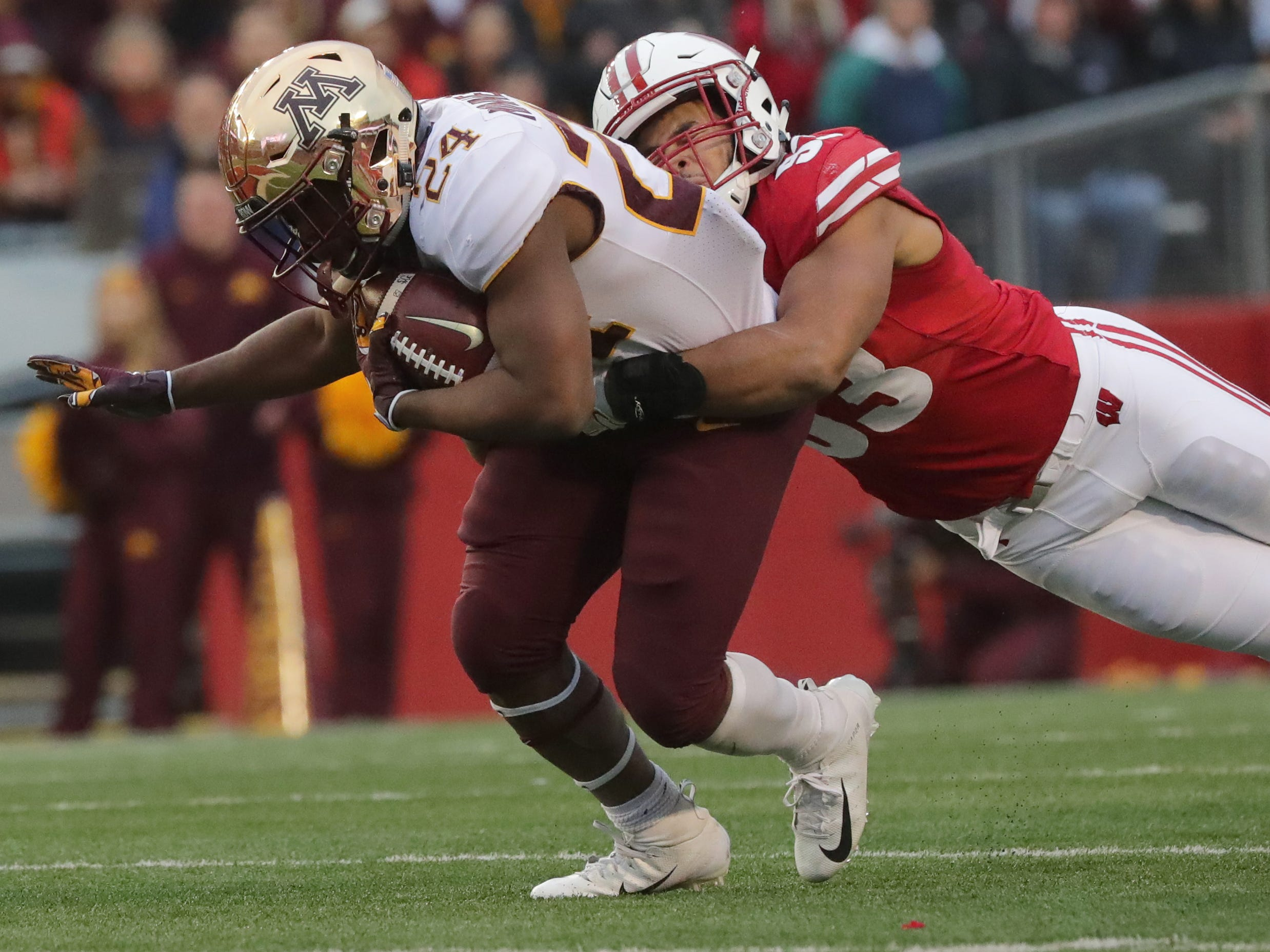 Minnesota running back Mohamed Ibrahim picks up a first down before being tackled by Wisconsin linebacker T.J. Edwards during the first quarter Saturday.