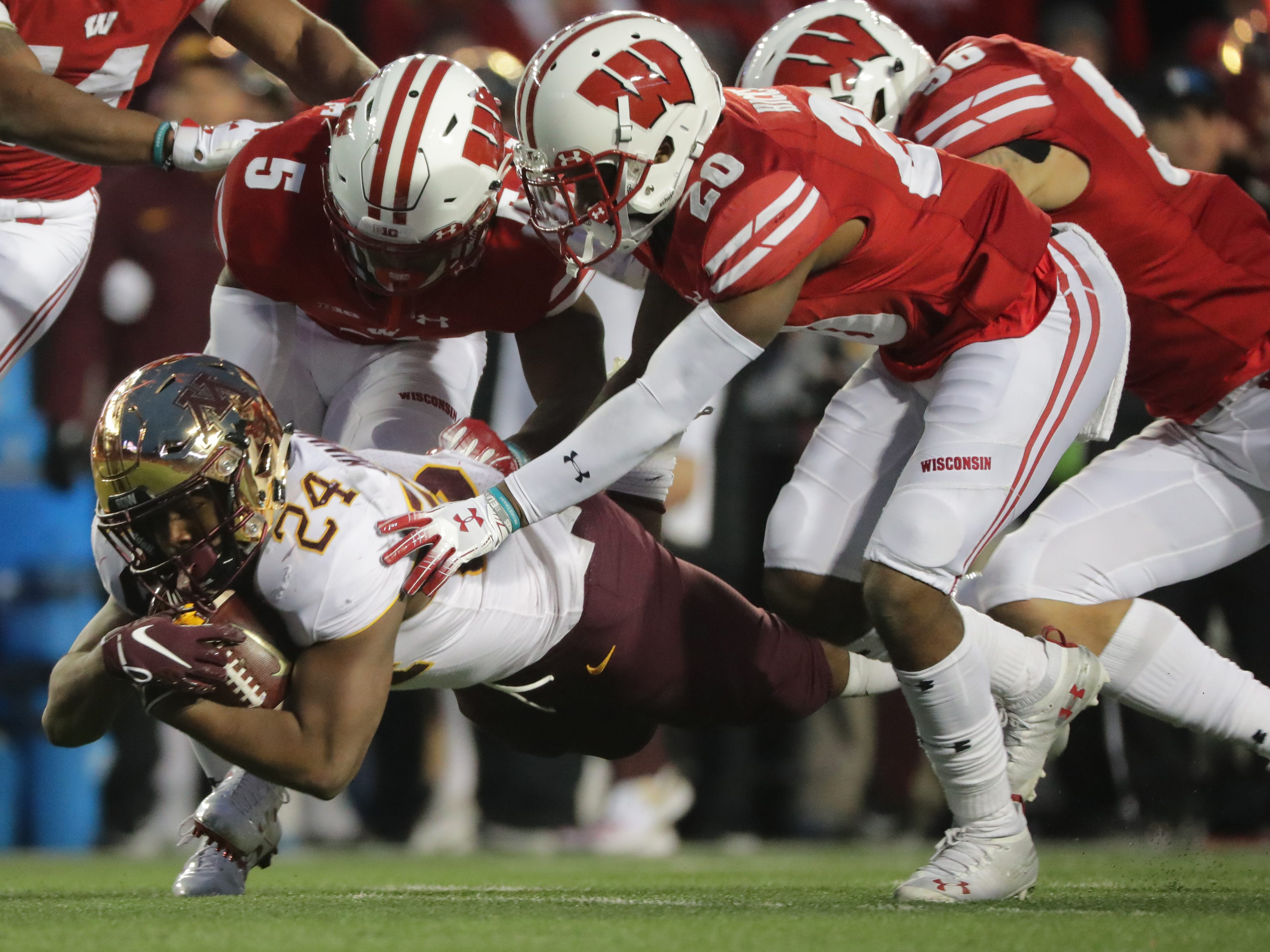 A host of Wisconsin defensive players take down Minnesota running back Mohamed Ibrahim but not until he picked up a first down during the third quarter on Saturday.