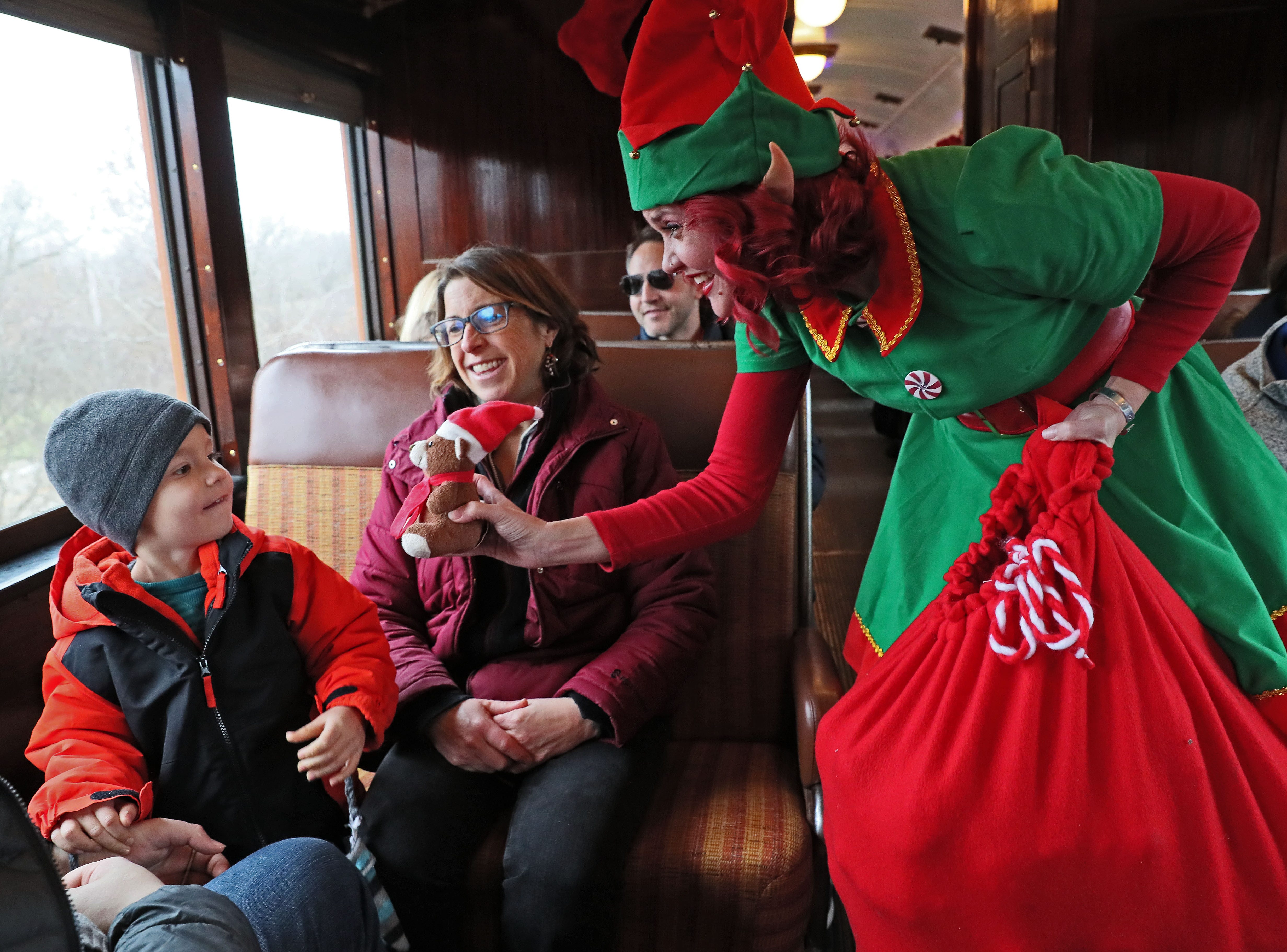 Anna Gleason, Santa's elf, offers a stuffed animal from her gift bag to Aidan Puczylowski, 3, of Milwaukee as his grandmother Laurie Due of Milwaukee looks on.
