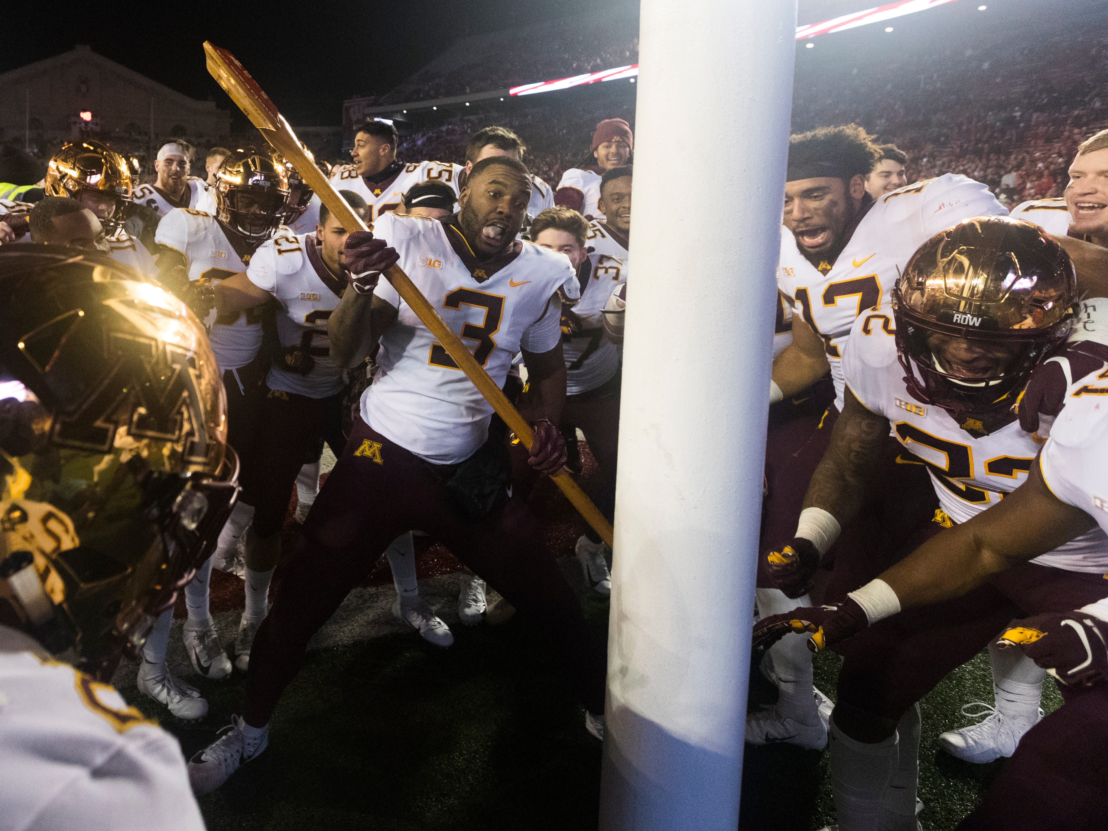 Minnesota defensive lineman Jerry Gibson uses Paul Bunyan's Axe to cut down a goalpost after the Gophers beat Wisconsin on Saturday.