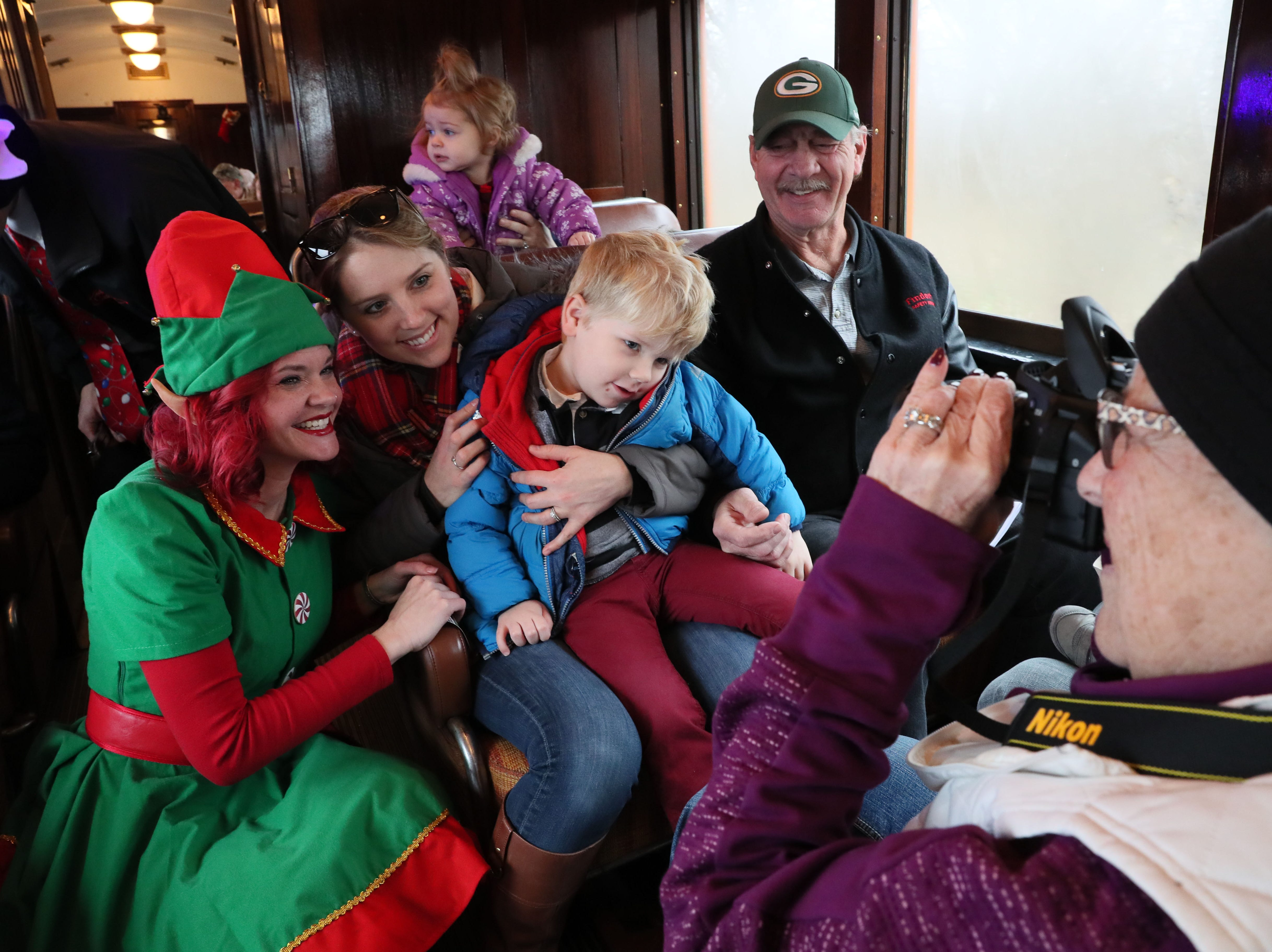 Santa's elf, Anna Gleason, poses with Danielle Wampole of Lake Mills and her  son, Emmett, 3, as his grandfather Doug Wampole of Madison looks on. Grandmother Alice Wampole takes their photo.