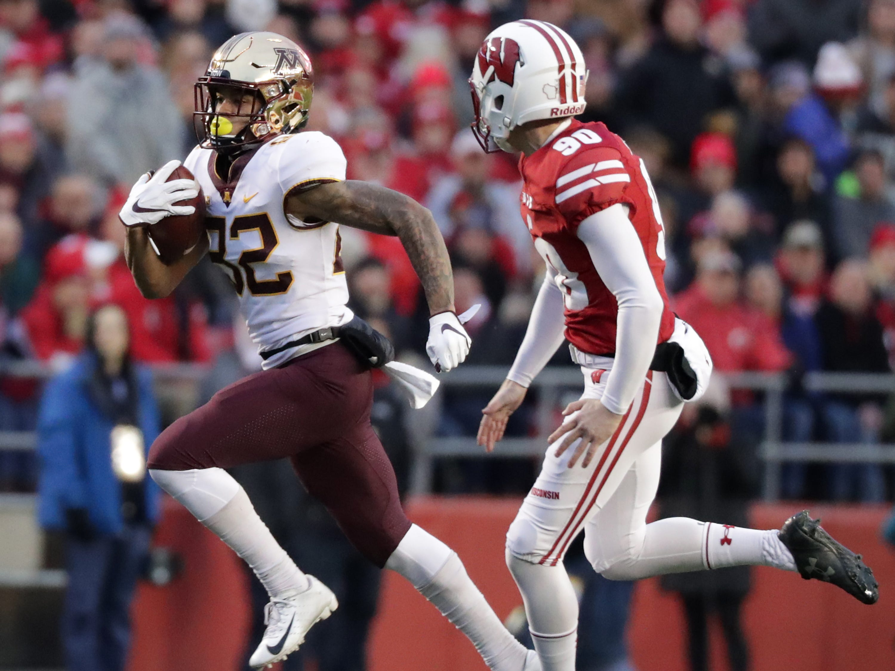 Demetrius Douglas of Minnesota outraces Wisconsin punter Connor Allen on a 69 yard punt return for a touchdown in the second quarter Saturday.