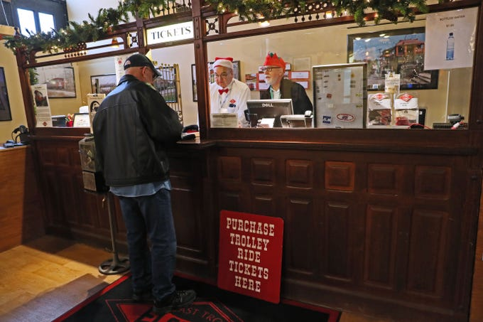 Bob Usarek (left rear) and Patrick Barney  sell tickets to a passengers at the depot in East Troy. Passengers took the East Troy Electric Railroad's Christmas Train from the depot in East Troy to The Elegant Farmer in Mukwonago. There they met Santa and had hot cider, hot chocolate, Christmas cookies and other treats before heading back to East Troy.