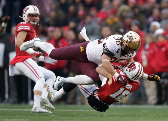 UW's Jack Dunn is leveled by Blake Cashman immediately after receiving a punt during the second quarter Saturday. Cashman was penalized on the play for targeting on the play and was ejected from the game.