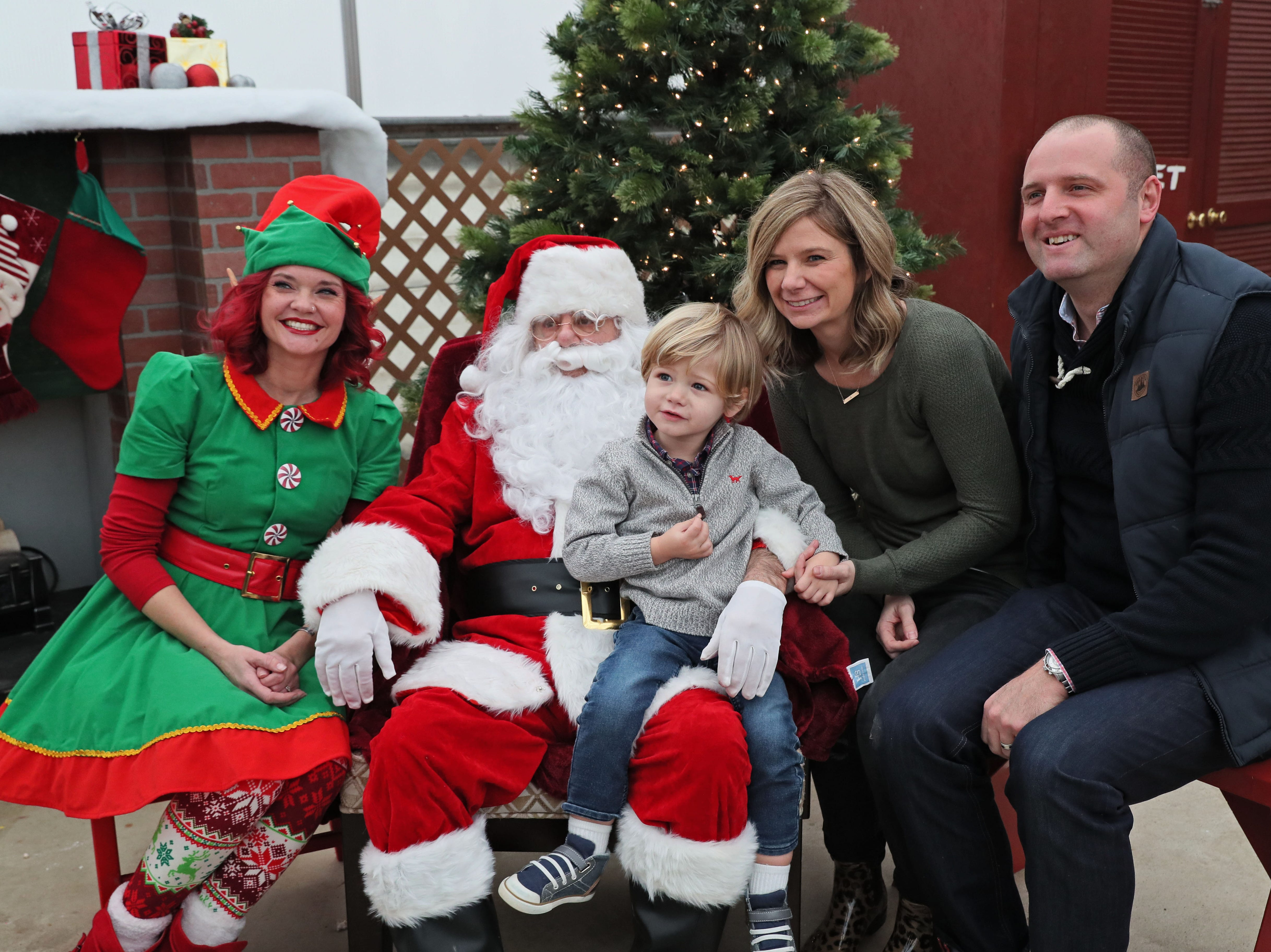 Kaaren Adam, her son Asher, 2, and husband Bill, all of Johnson Creek, pose for a photo with Santa (Blase Catanese) and his elf ( Anna Gleason) at The Elegant Farmer.