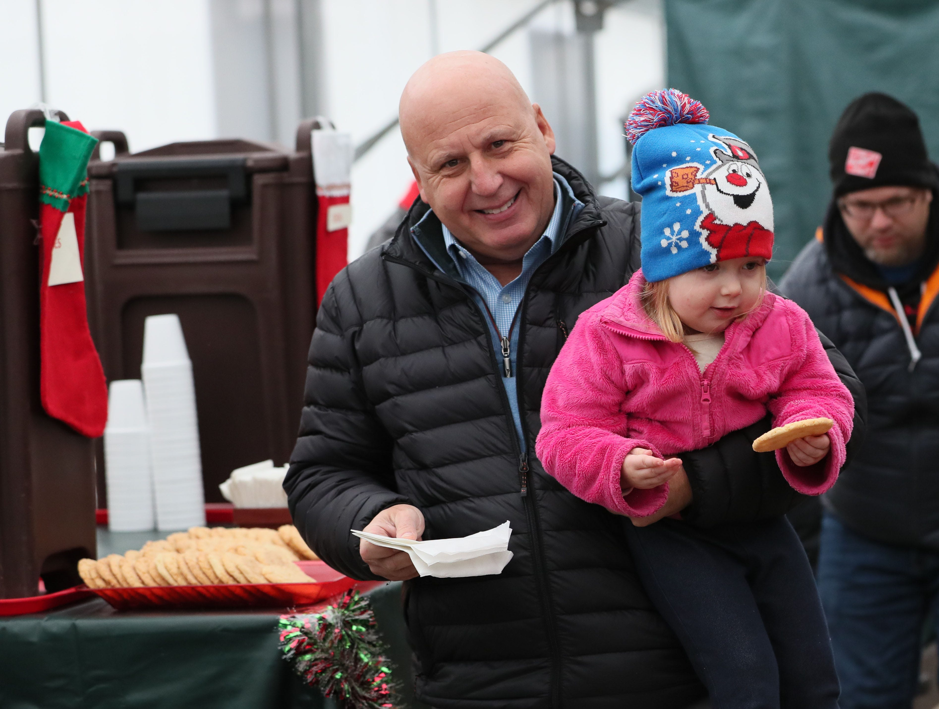Tom Hoppe of Franklin carries his granddaughter Lucy Meerkins, 2, of Franklin after getting a cookie at The Elegant Farmer.