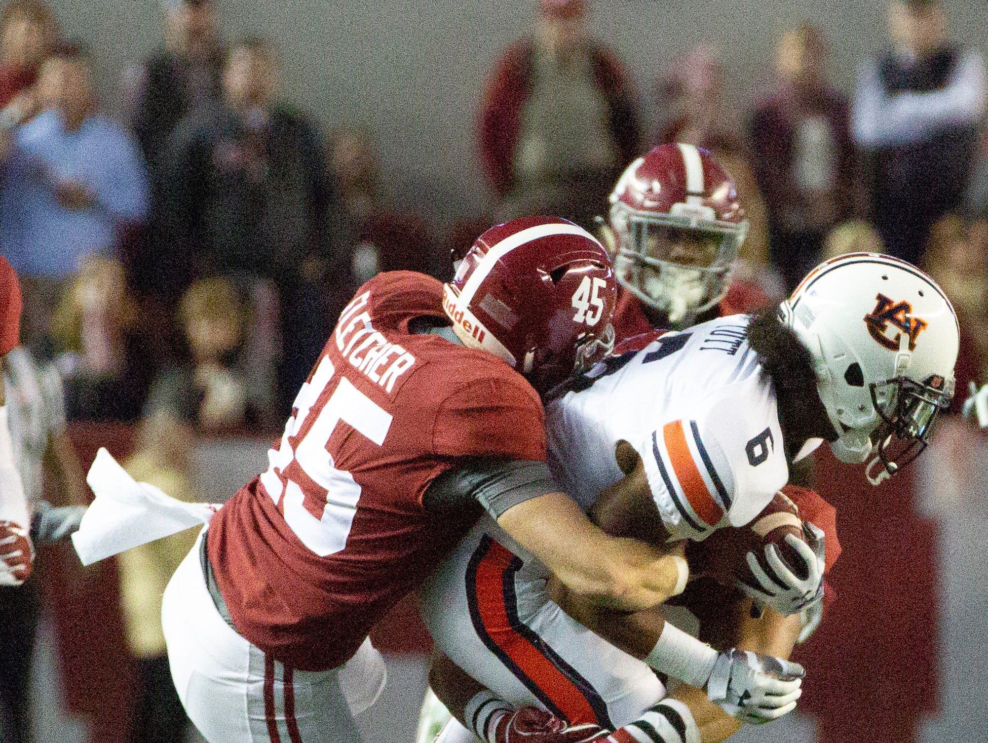 Alabama's Thomas Fletcher takes down Auburn's Christian Tutt during a play in the third quarter.
