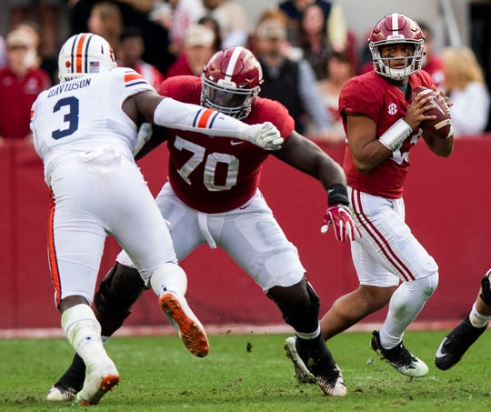 Alabama quarterback Tua Tagovailoa (13) looks to pass behind the blocking of offensive lineman Alex Leatherwood (70) in first half action during the Iron Bowl at Bryant-Denny Stadium in Tuscaloosa, Ala., on Saturday November 24, 2018.