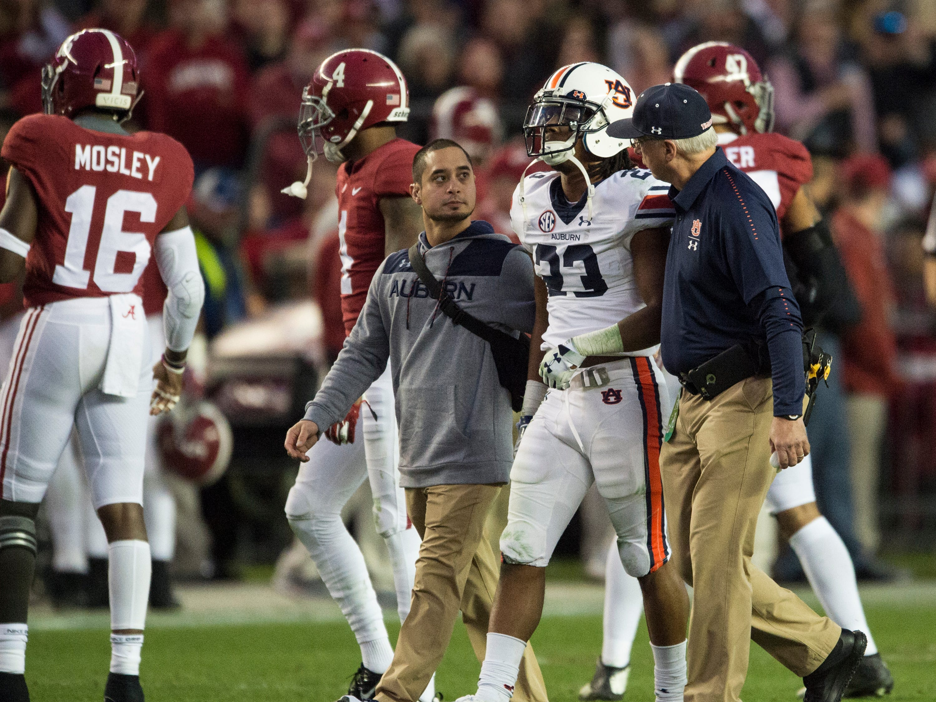 Auburn wide receiver Ryan Davis (23) walks off the field after sustaining an injury during the Iron Bowl at Bryant-Denny Stadium in Tuscaloosa, Ala., on Saturday, Nov. 24, 2018. Alabama defeated Auburn 52-21.
