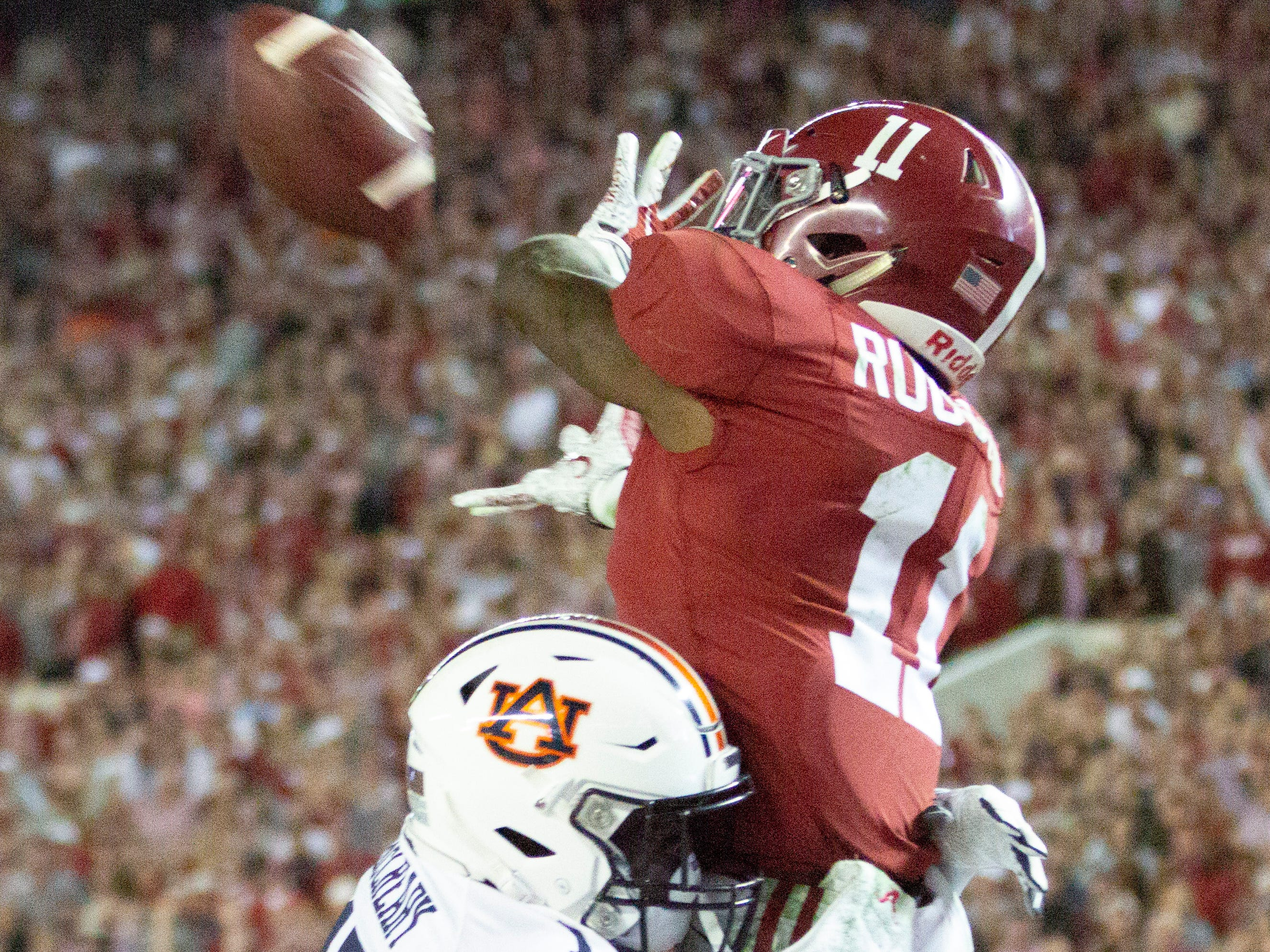 Alabama's Henry Ruggs III makes a catch in the fourth quarter despite Roger McCreary's best efforts.