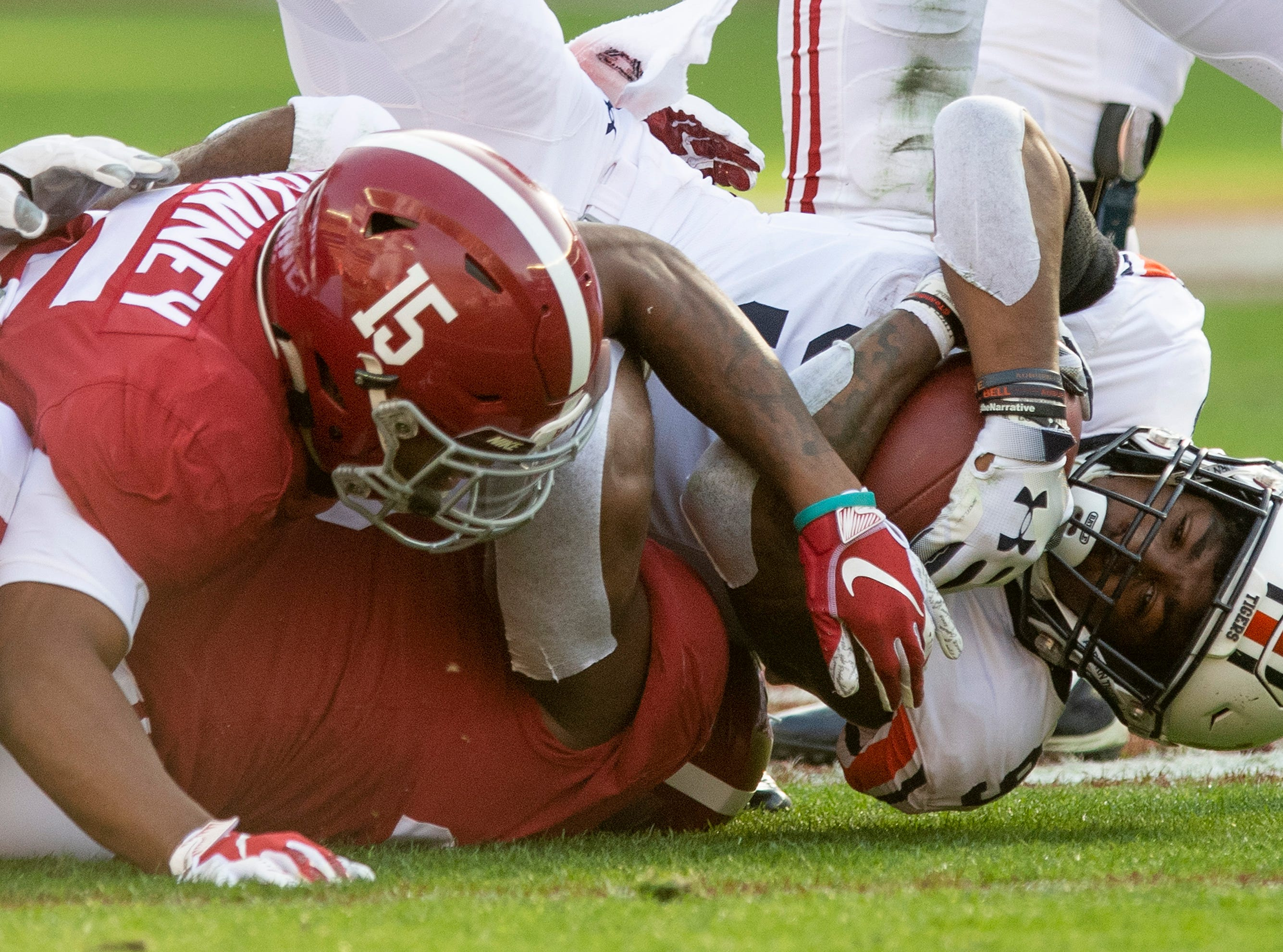 Auburn running back Kam Martin (9) is stopped by Alabama defensive lineman Isaiah Buggs (49) and defensive back Xavier McKinney (15) in first half action during the Iron Bowl at Bryant-Denny Stadium in Tuscaloosa, Ala., on Saturday November 24, 2018.