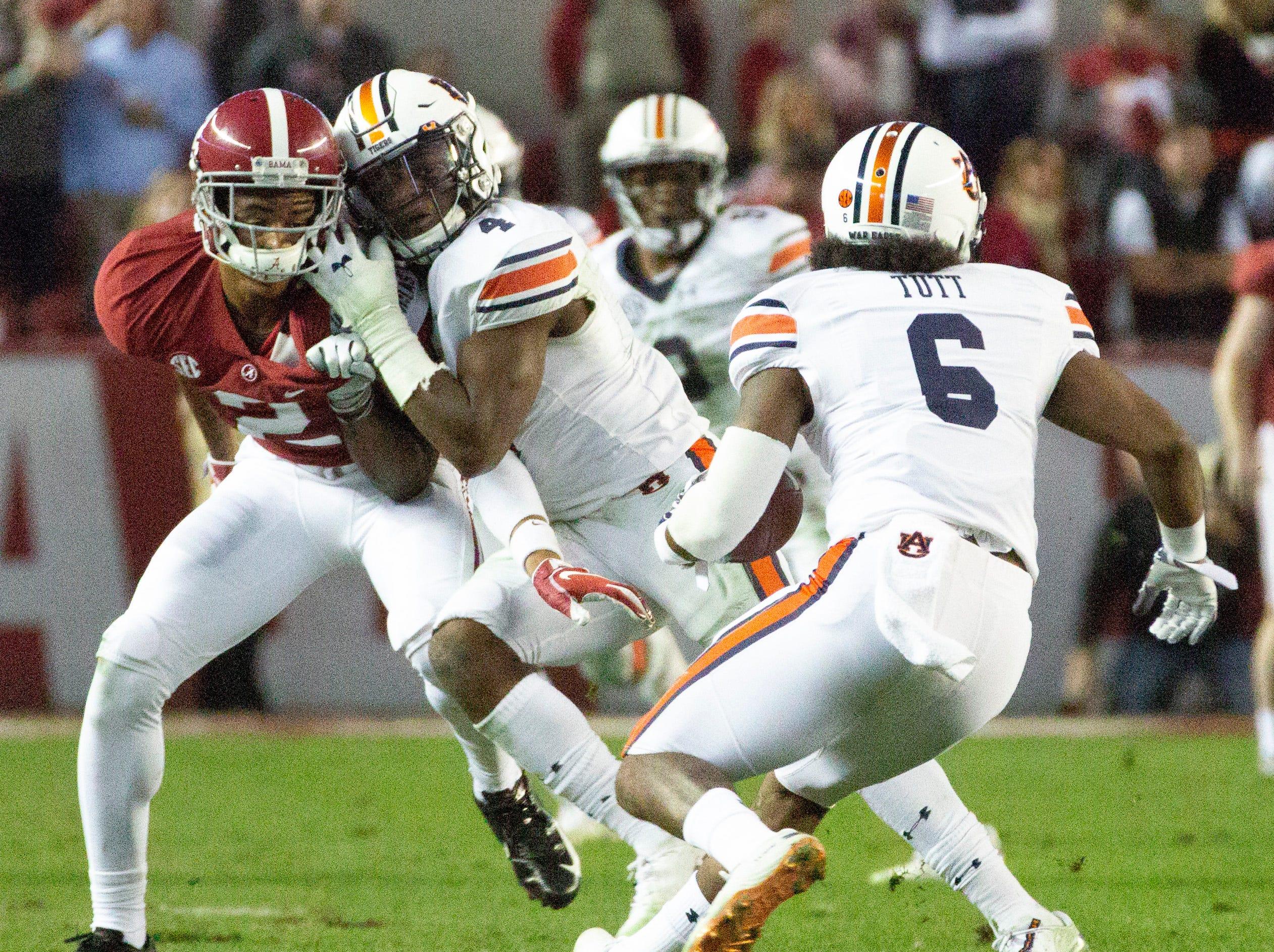 Auburn's Noah Igbinoghene gives Alabama's Patrick Surtain II a hug as the Tigers' Christian Tutt runs the ball.