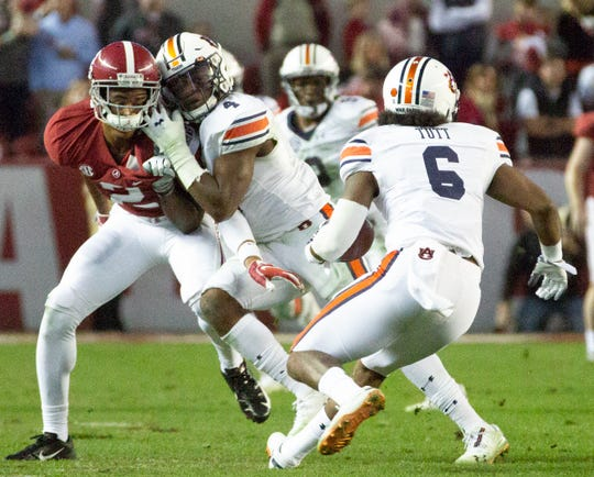 Auburn's Noah Igbinoghene (4) blocks Alabama's Patrick Surtain II as Christian Tutt (6) returns a punt during the Iron Bowl on Nov. 24, 2018, in Tuscaloosa.