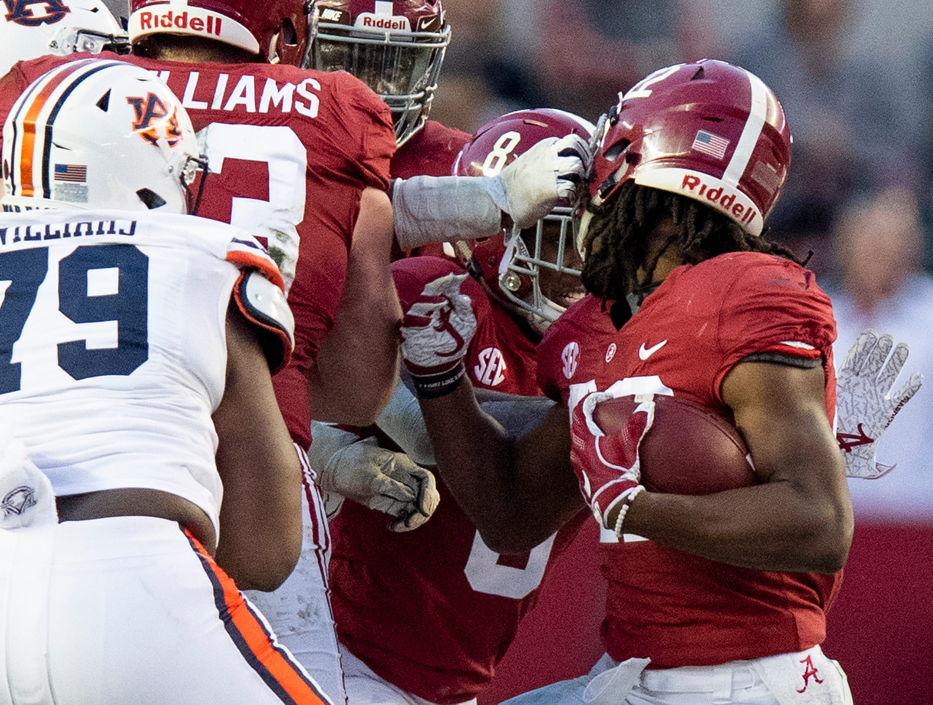 Alabama running back Najee Harris (22) is face masked as he carries the ball against Auburn in second half action during the Iron Bowl at Bryant-Denny Stadium in Tuscaloosa, Ala., on Saturday November 24, 2018.