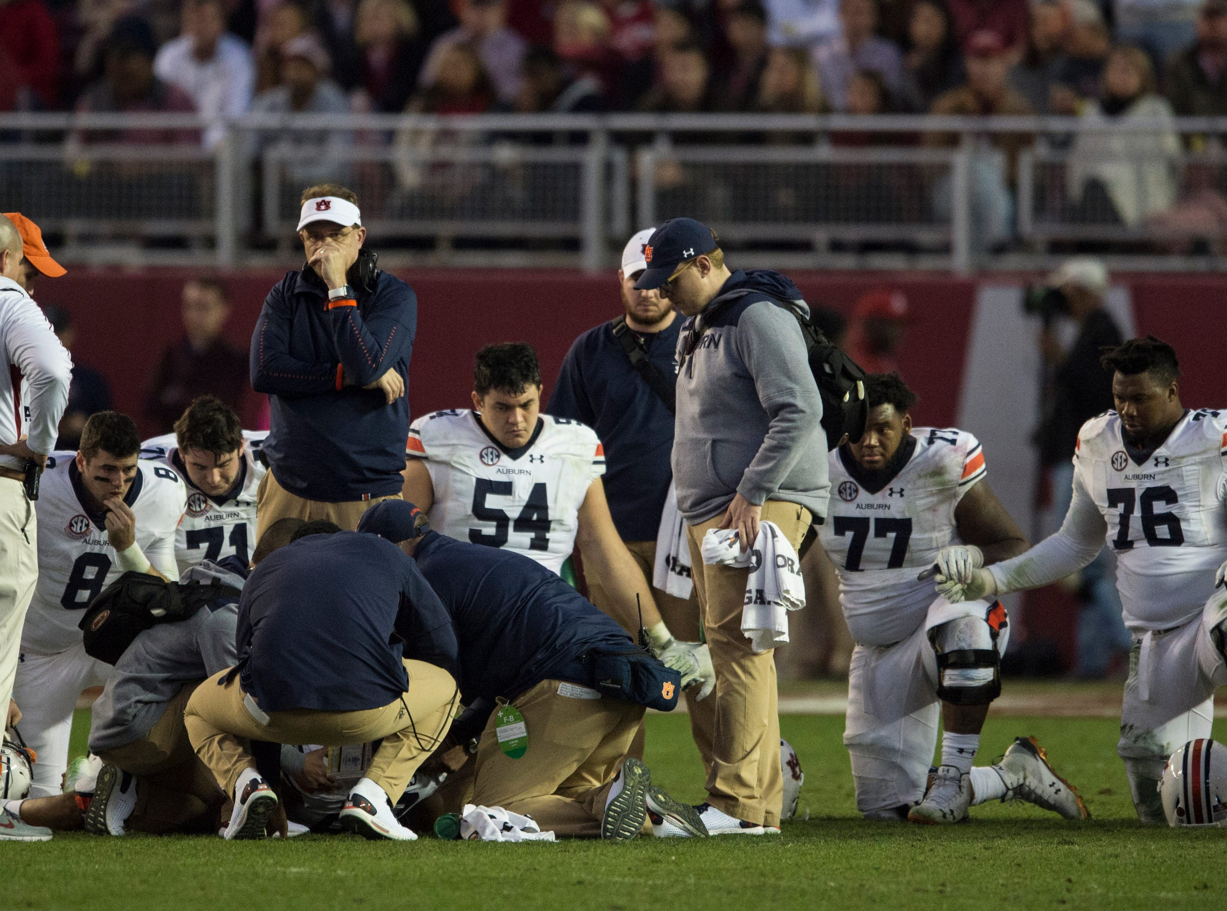 Auburn players and coaches surround Auburn wide receiver Ryan Davis (23) after he sustain an injury during the Iron Bowl at Bryant-Denny Stadium in Tuscaloosa, Ala., on Saturday, Nov. 24, 2018. Alabama defeated Auburn 52-21.