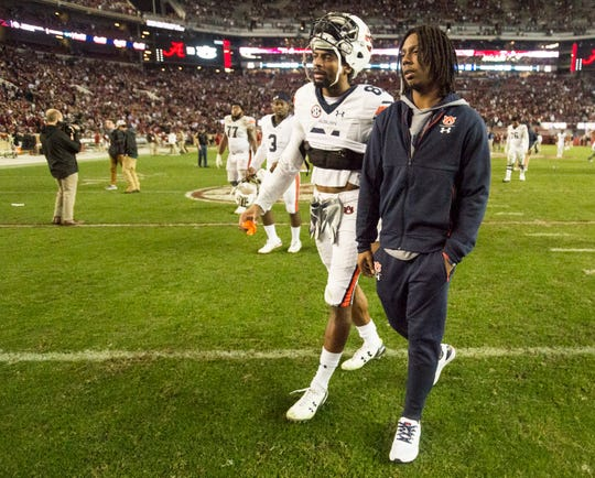 Auburn wide receiver Darius Slayton (81) and Auburn wide receiver Ryan Davis (23) walk of the field after the Iron Bowl at Bryant-Denny Stadium in Tuscaloosa, Ala., on Saturday, Nov. 24, 2018. Alabama defeated Auburn 52-21. Davis was injured during the game.