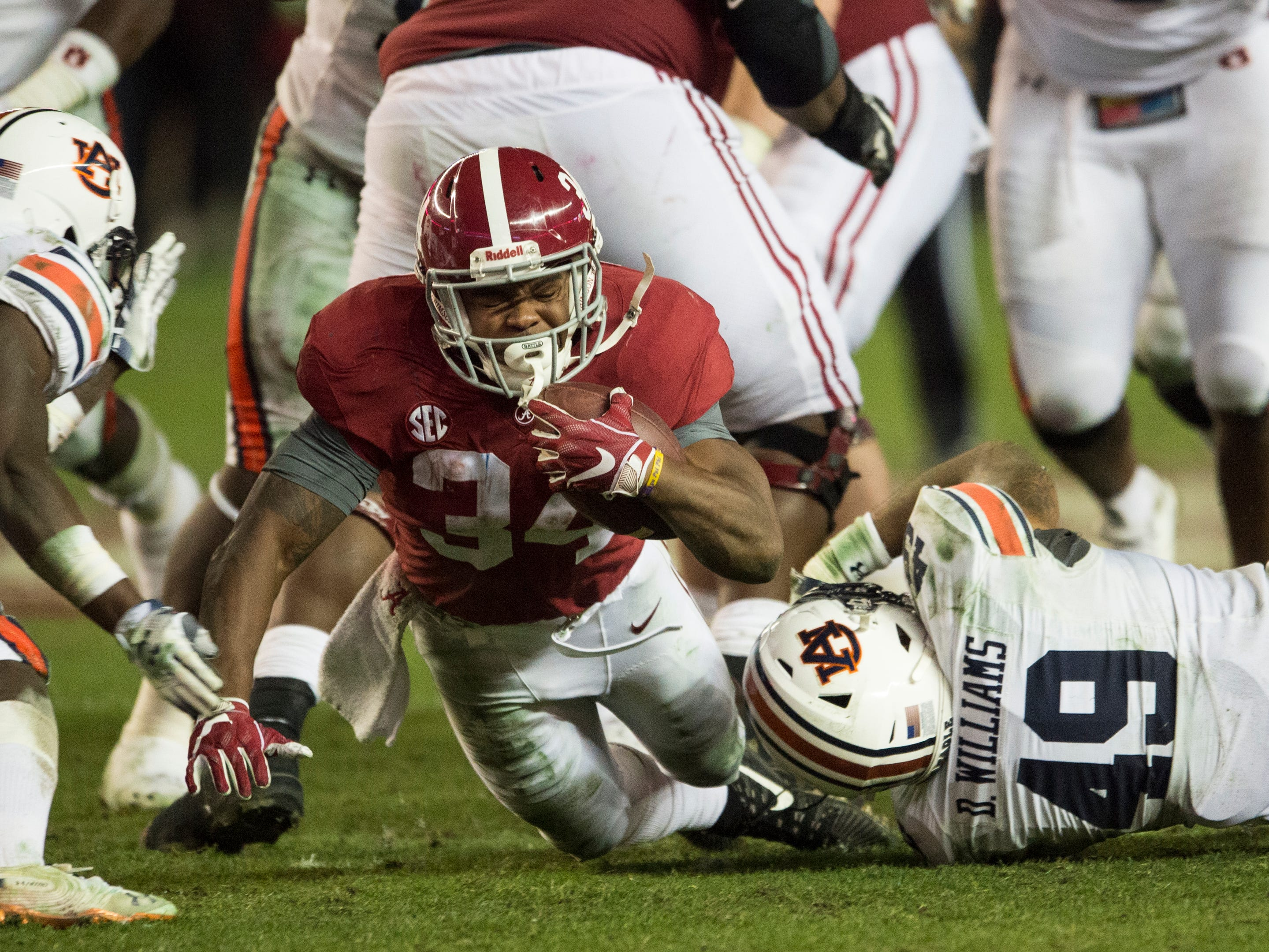 Alabama running back Damien Harris (34) is taken down by Auburn linebacker Darrell Williams (49) during the Iron Bowl at Bryant-Denny Stadium in Tuscaloosa, Ala., on Saturday, Nov. 24, 2018. Alabama defeated Auburn 52-21.