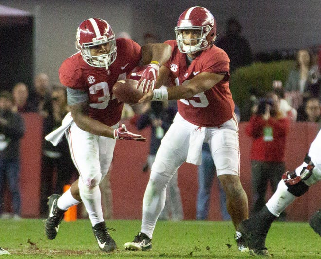 Alabama's Tua Tagovailoa passes the ball to Damien Harris during the third quarter.