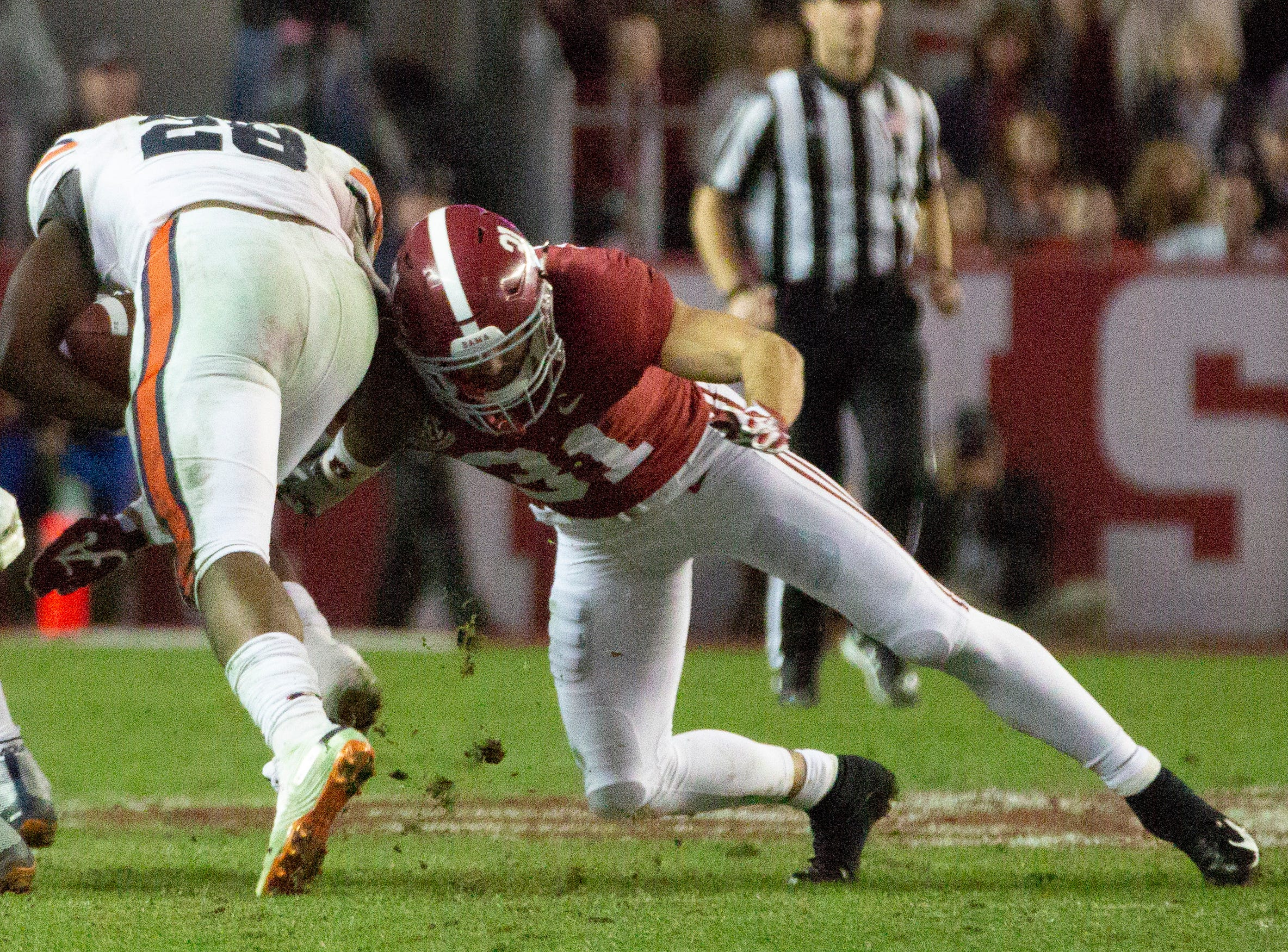 Auburn's JaTarvious Whitlow ducks down as Alabama's Keaton Anderson goes in for the tackle.