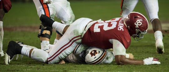 Alabama defensive lineman Quinnen Williams (92) lands on Auburn quarterback Jarrett Stidham (8) after he throws the ball during the Iron Bowl at Bryant-Denny Stadium in Tuscaloosa, Ala., on Saturday, Nov. 24, 2018. Alabama defeated Auburn 52-21. A roughing the passer penalty was called on Williams on the play.