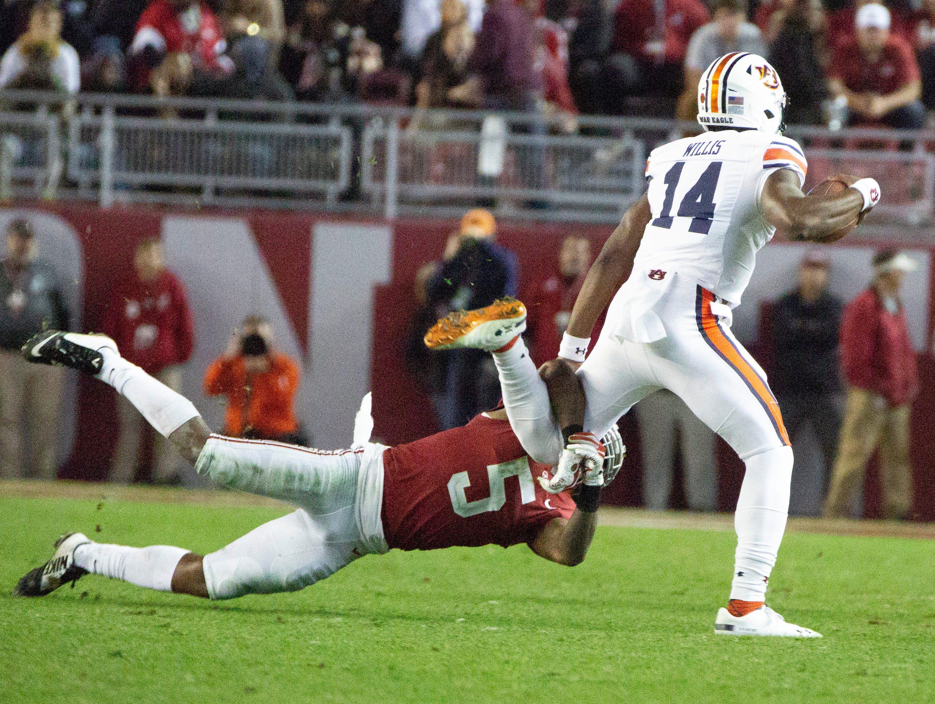 Alabama's Shyheim Carter grabs ahold of Auburn's Malik Willis' leg for a tackle in the fourth quarter.