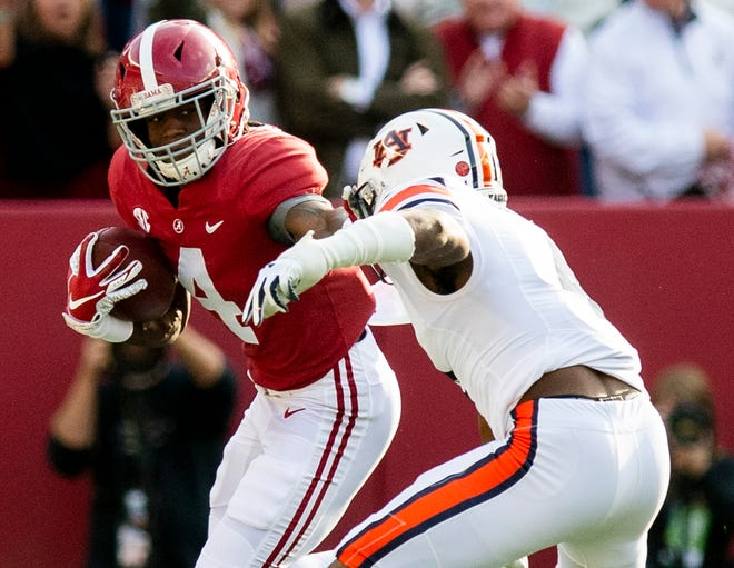 Alabama wide receiver Jerry Jeudy (4) stiff arms Auburn defensive back Noah Igbinoghene (4) in first half action during the Iron Bowl at Bryant-Denny Stadium in Tuscaloosa, Ala., on Saturday November 24, 2018.
