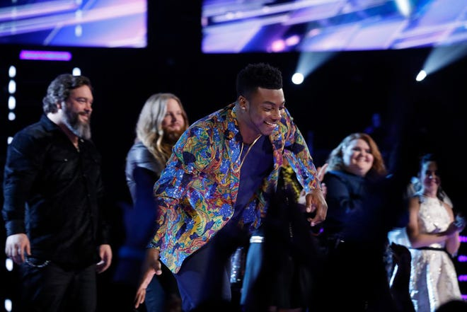 """Kirk Jay high-fives fans after being saved on Tuesday and moving into the top 11 on NBC's """"The Voice."""" He will perform again live on Monday, Nov. 26."""
