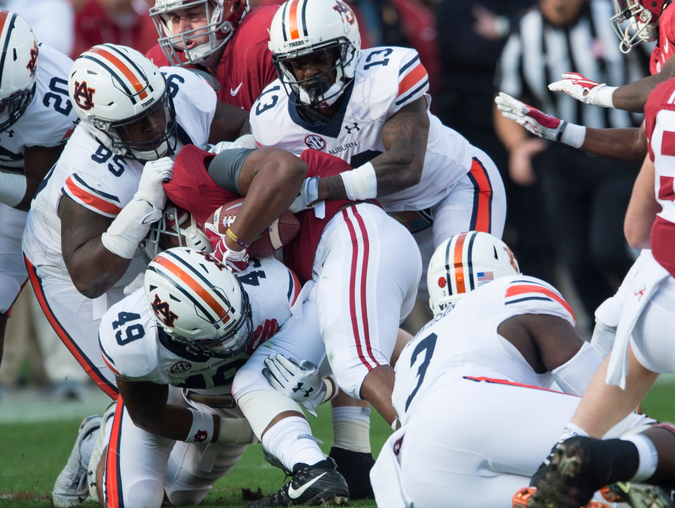 Alabama running back Damien Harris (34) is wrapped up by multiple Auburn defenders during the Iron Bowl at Bryant-Denny Stadium in Tuscaloosa, Ala., on Saturday, Nov. 24, 2018. Alabama leads Auburn 17-14 at halftime.