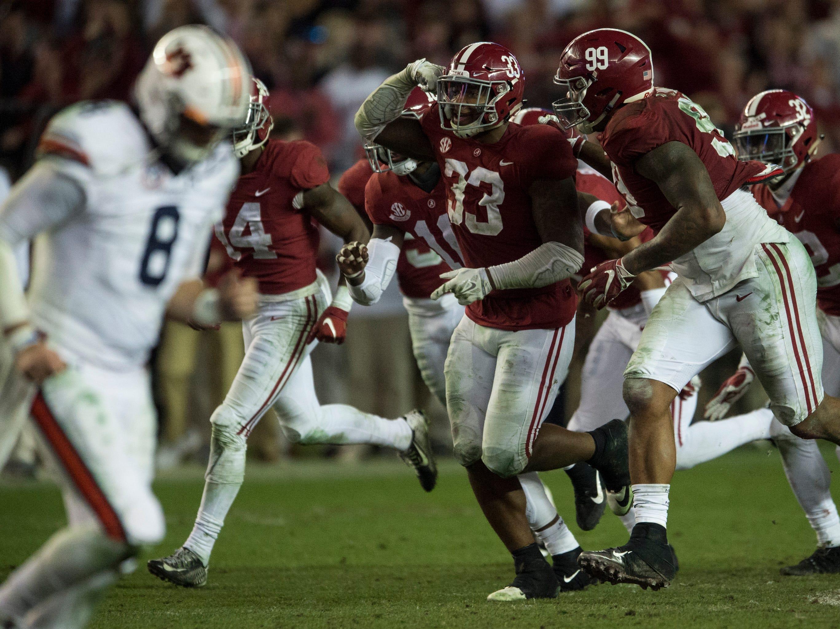 Alabama linebacker Anfernee Jennings (33) celebrates after intercepting the ball as Auburn quarterback Jarrett Stidham (8) runs off the field during the Iron Bowl at Bryant-Denny Stadium in Tuscaloosa, Ala., on Saturday, Nov. 24, 2018. Alabama defeated Auburn 52-21.