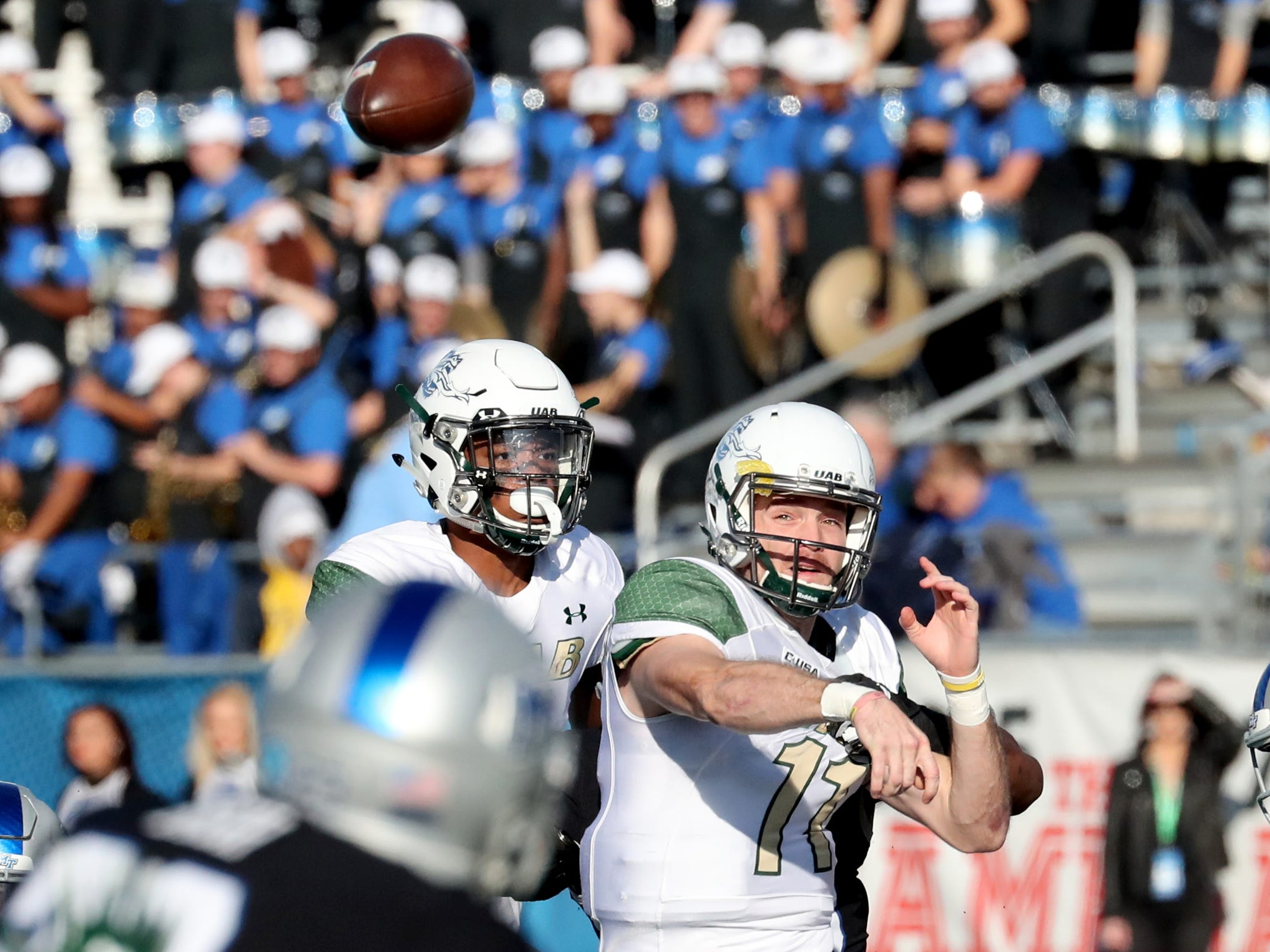 UAB's quarterback AJ Erdely (11) passes the ball as MTSU's Darius Harris (30) grabs him from behind during the game at MTSU on Saturday, Nov. 24, 2018.