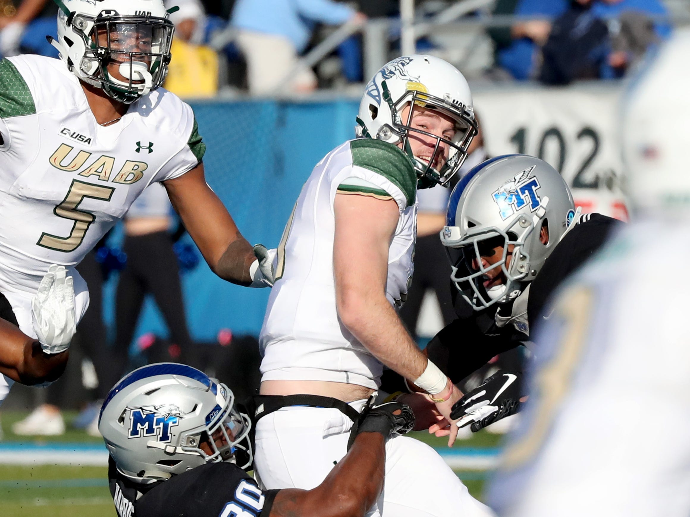 UAB's quarterback AJ Erdely (11) watches hs pass as MTSU's Darius Harris (30) grabs him from behind during the game at MTSU on Saturday, Nov. 24, 2018.