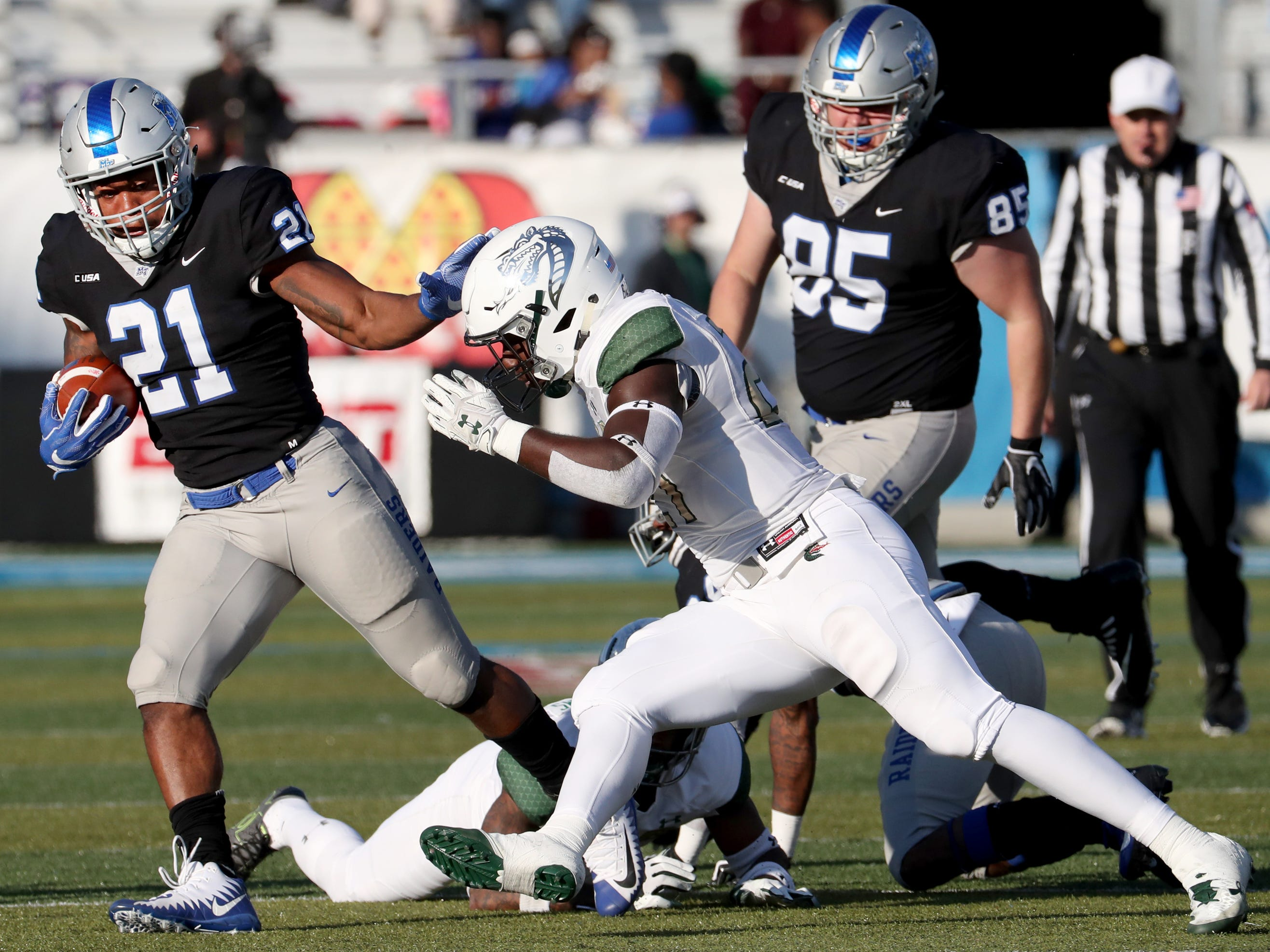 MTSU's Tavares Thomas (21) runs the ball as UAB's Chris Woolbright (27) moves in for a tackle during the game at MTSU on Saturday, Nov. 24, 2018.