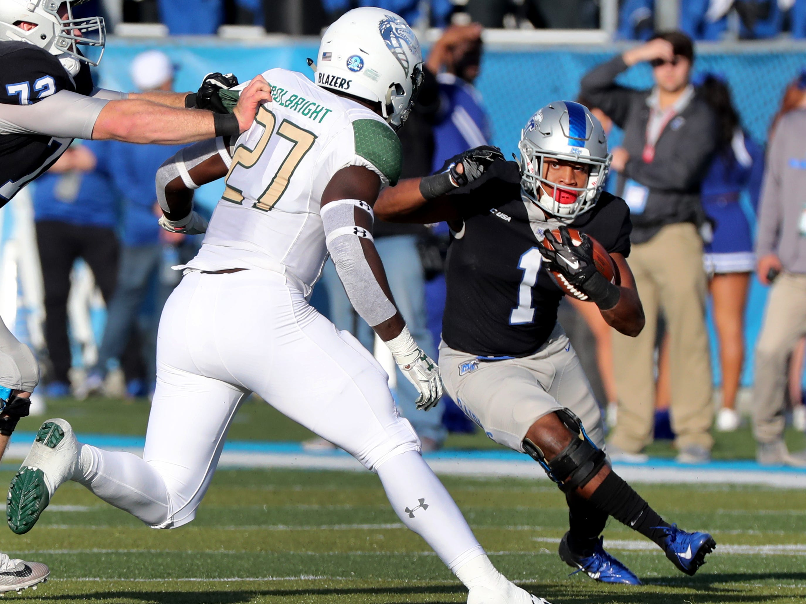 MTSU's Terelle West (1) runs the ball as UAB's Chris Woolbright (27) moves in for a tackle during the game at MTSU on Saturday, Nov. 24, 2018.
