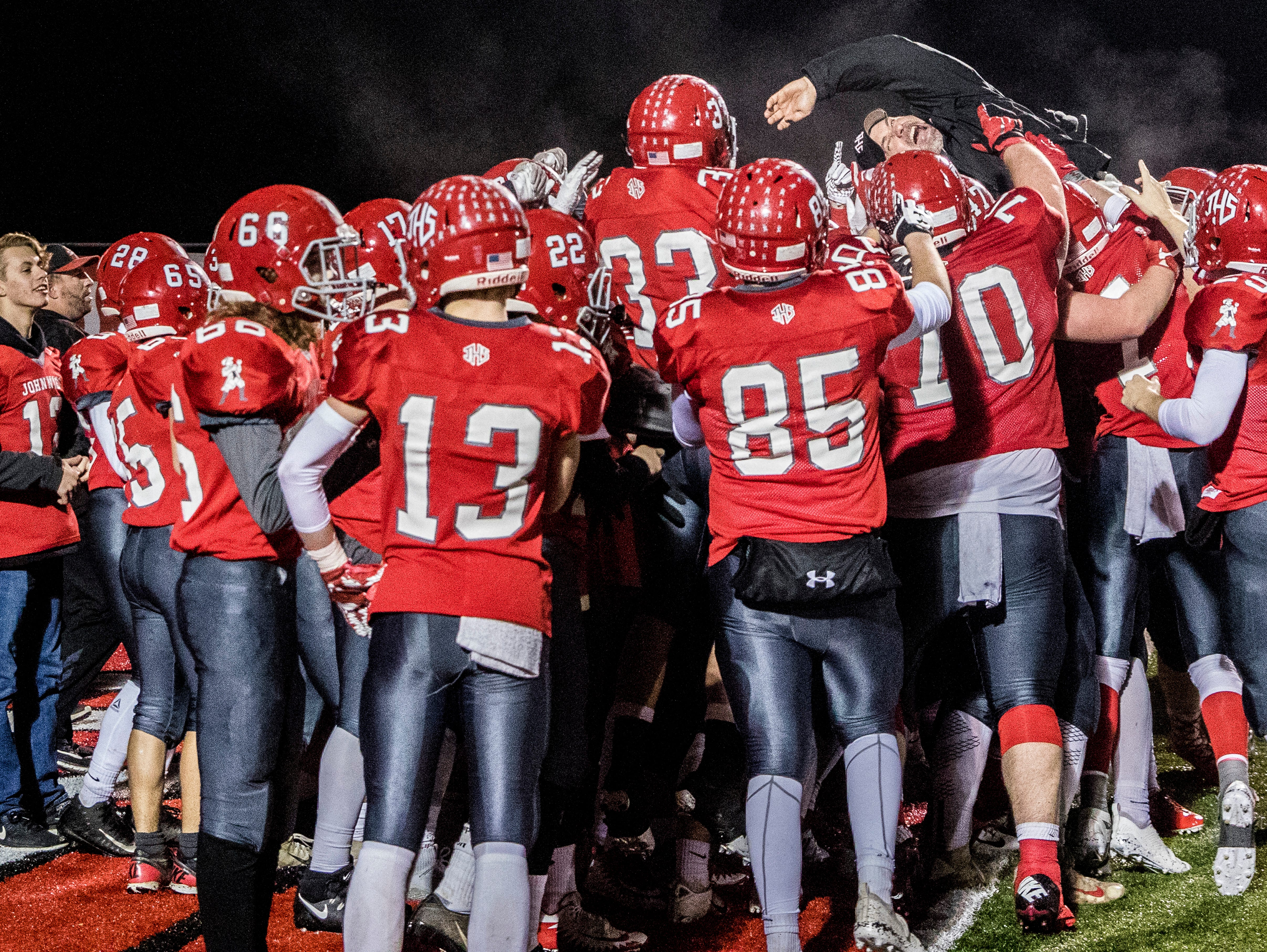 Coach Mike Carter bodysurfs with his team after making a charging jump Saturday night in Jackson, Ohio, after winning against Wheelersburg 32-14 in a Division V state semifinal.