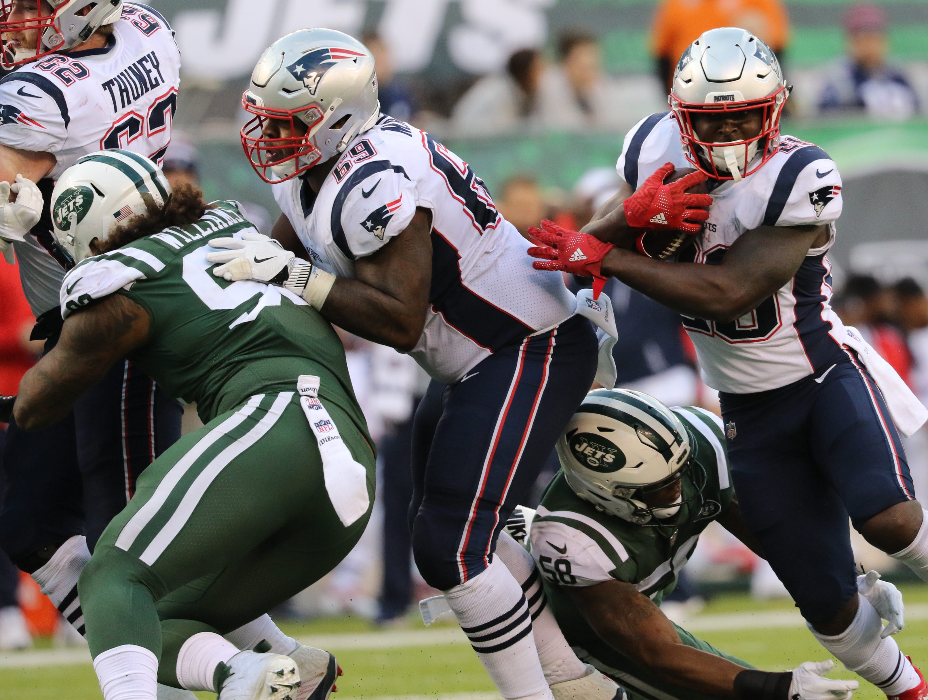 James White runs the ball for the Patriots as he tries to break a tackle attempt by Darron Lee, of the Jets, during the second half. Sunday, November 25, 2018