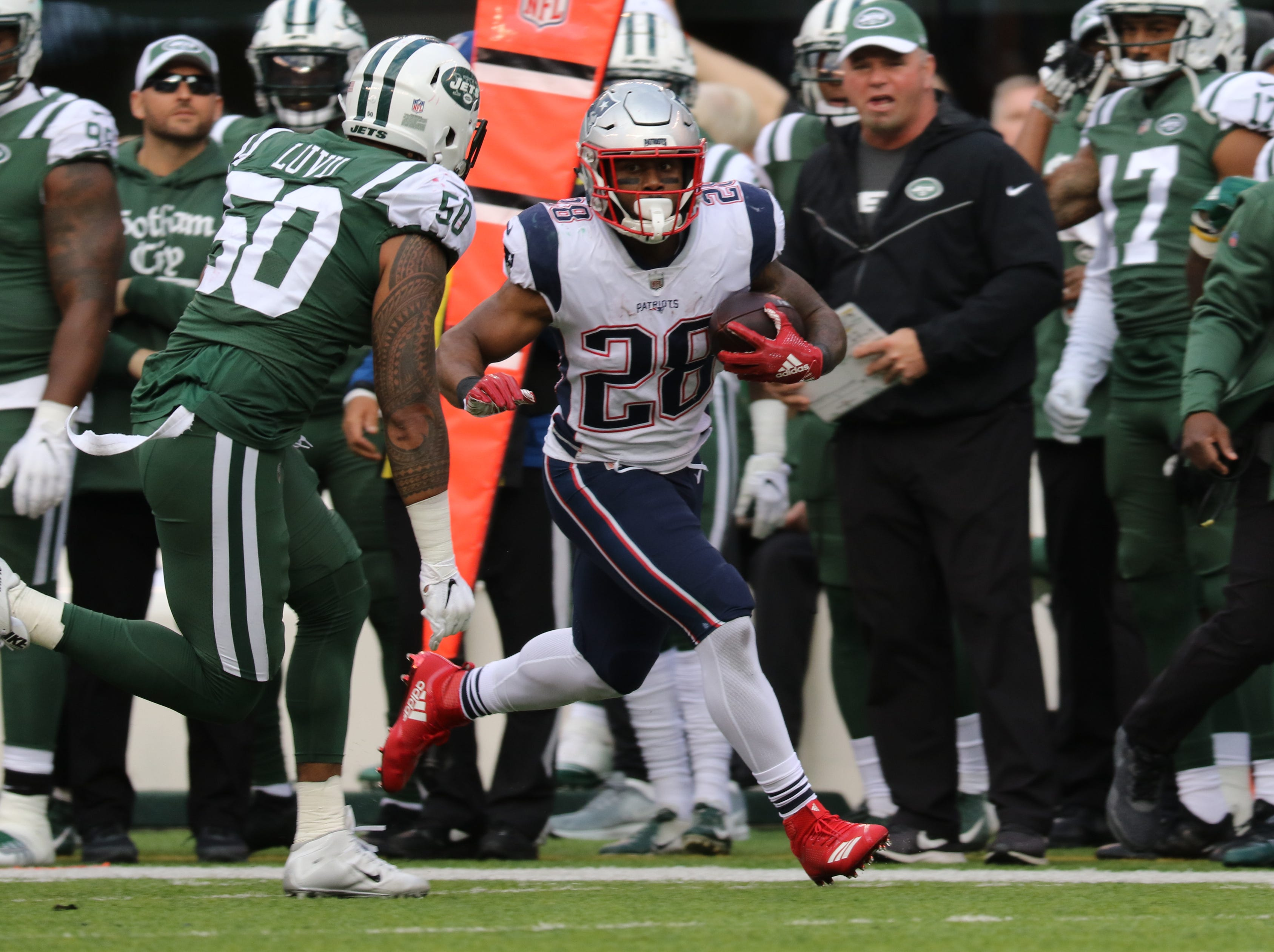 James White, of the Patriots, runs with the ball as Frankie Luvu plays defense for the Jets. November 25, 2018.