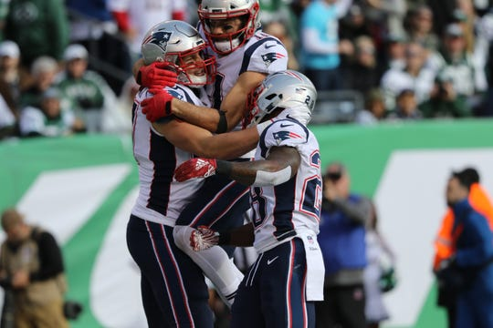 Rob Gronkowski, of the Patriots is congratulated by his teammates, Julian Edleman and James White, after scoring a first half touchdown. Sunday, November 25, 2018